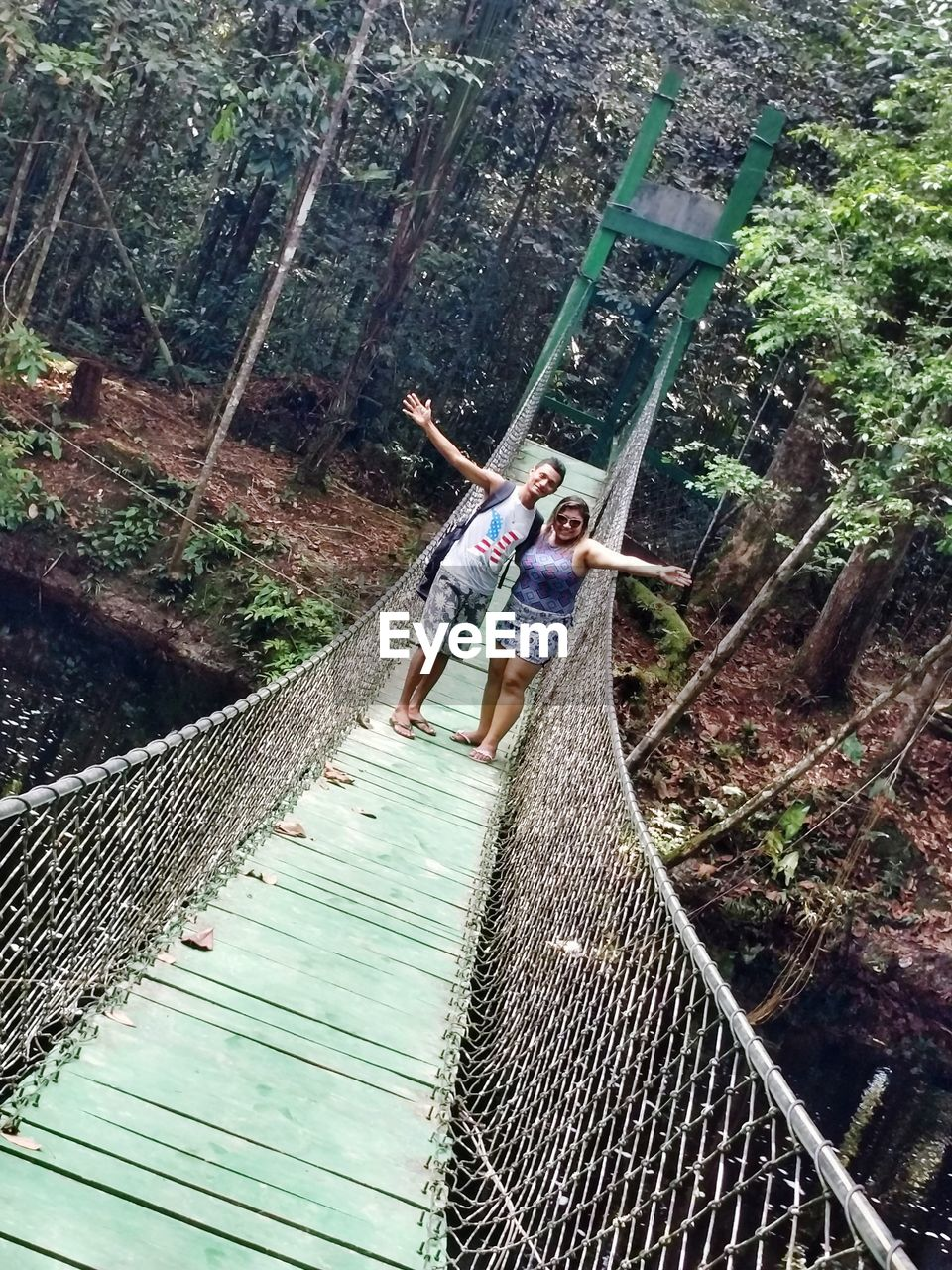 real people, casual clothing, leisure activity, day, outdoors, lifestyles, standing, tree, full length, footbridge, nature, forest, young adult, young women, people