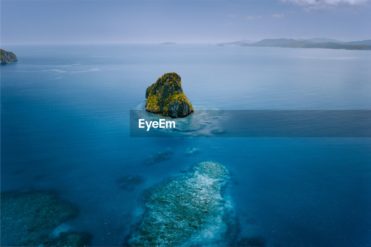 Scenic view of rock in sea against sky