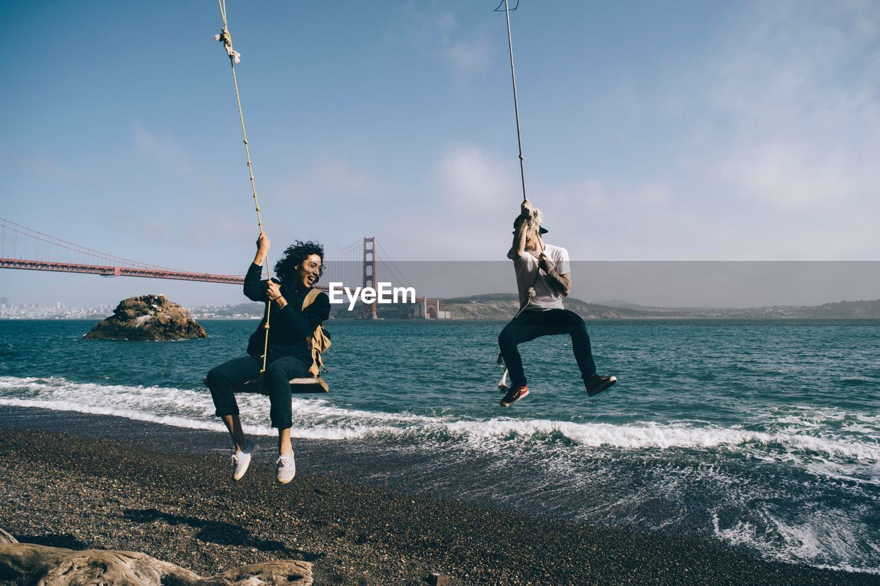 FULL LENGTH OF YOUNG FRIENDS AGAINST SEA