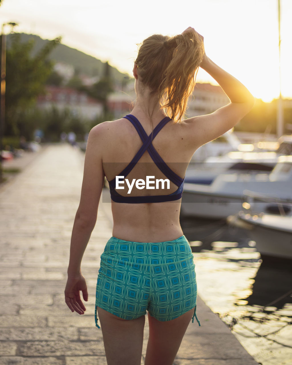 Rear view of woman standing in city in yoga clothes