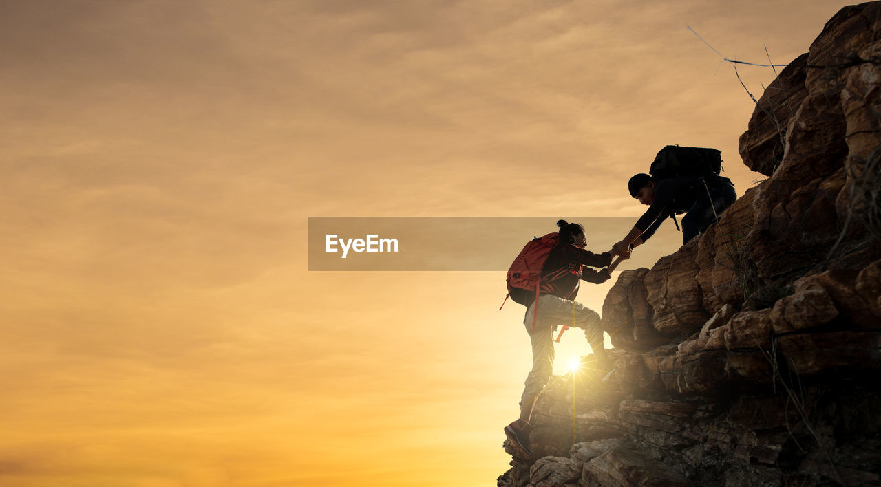 Man assisting friend in climbing on rock against sky during sunset