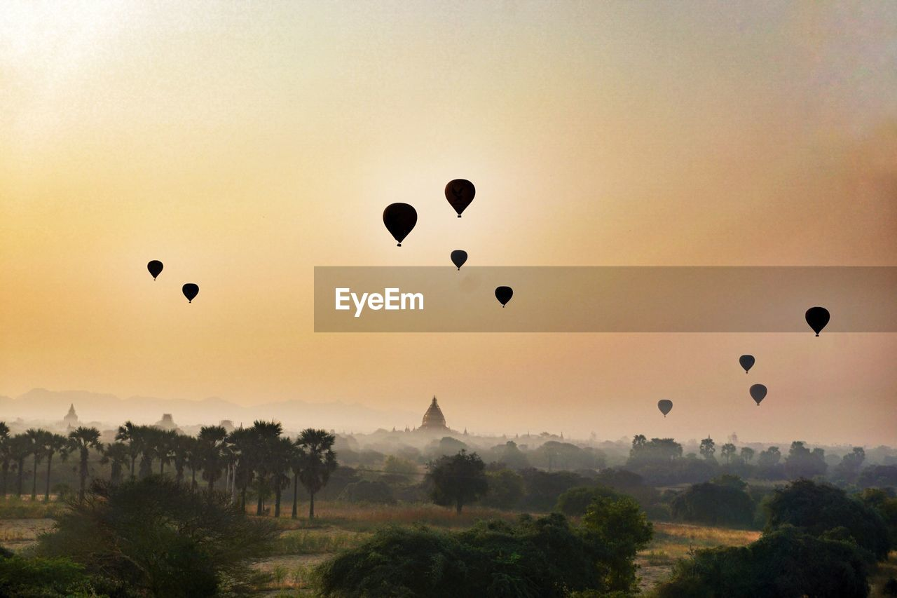 sky, hot air balloon, balloon, air vehicle, sunset, mid-air, nature, beauty in nature, flying, scenics - nature, plant, tree, transportation, travel destinations, travel, silhouette, tourism, tranquil scene, tranquility, place of worship, no people, sun, outdoors