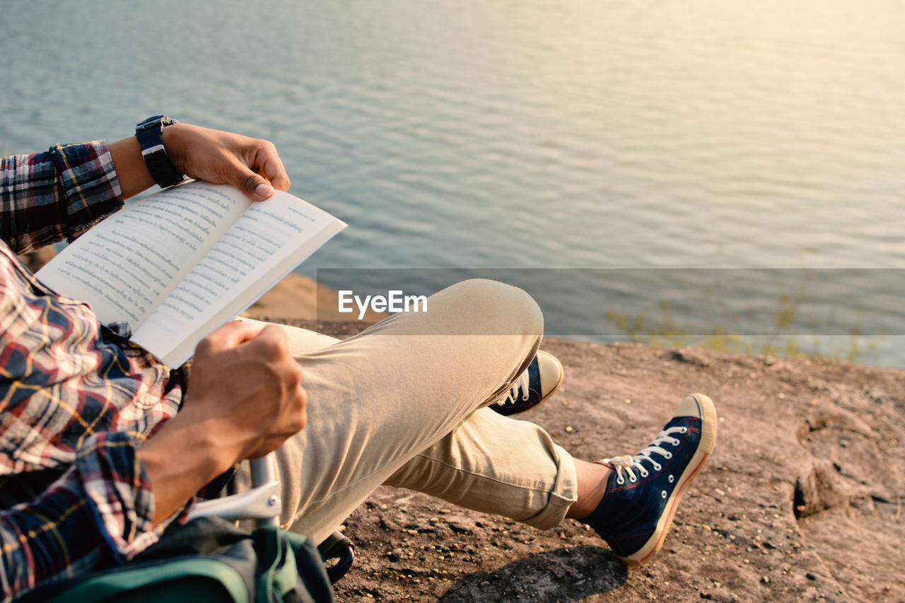 Midsection Of Man Reading Book On Waterfront