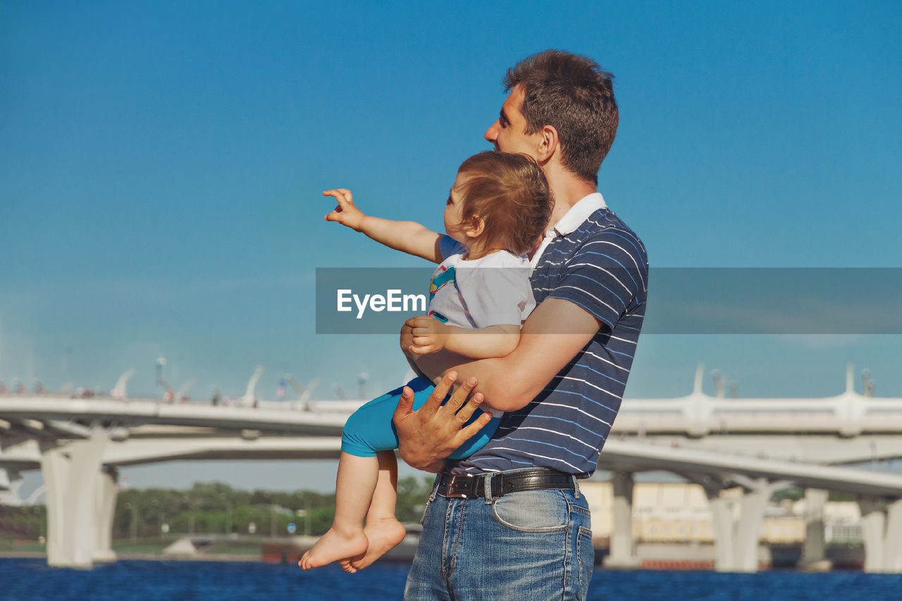 Dad joyfully clings to his daughter two years  against blue sky child shows with right hand to left