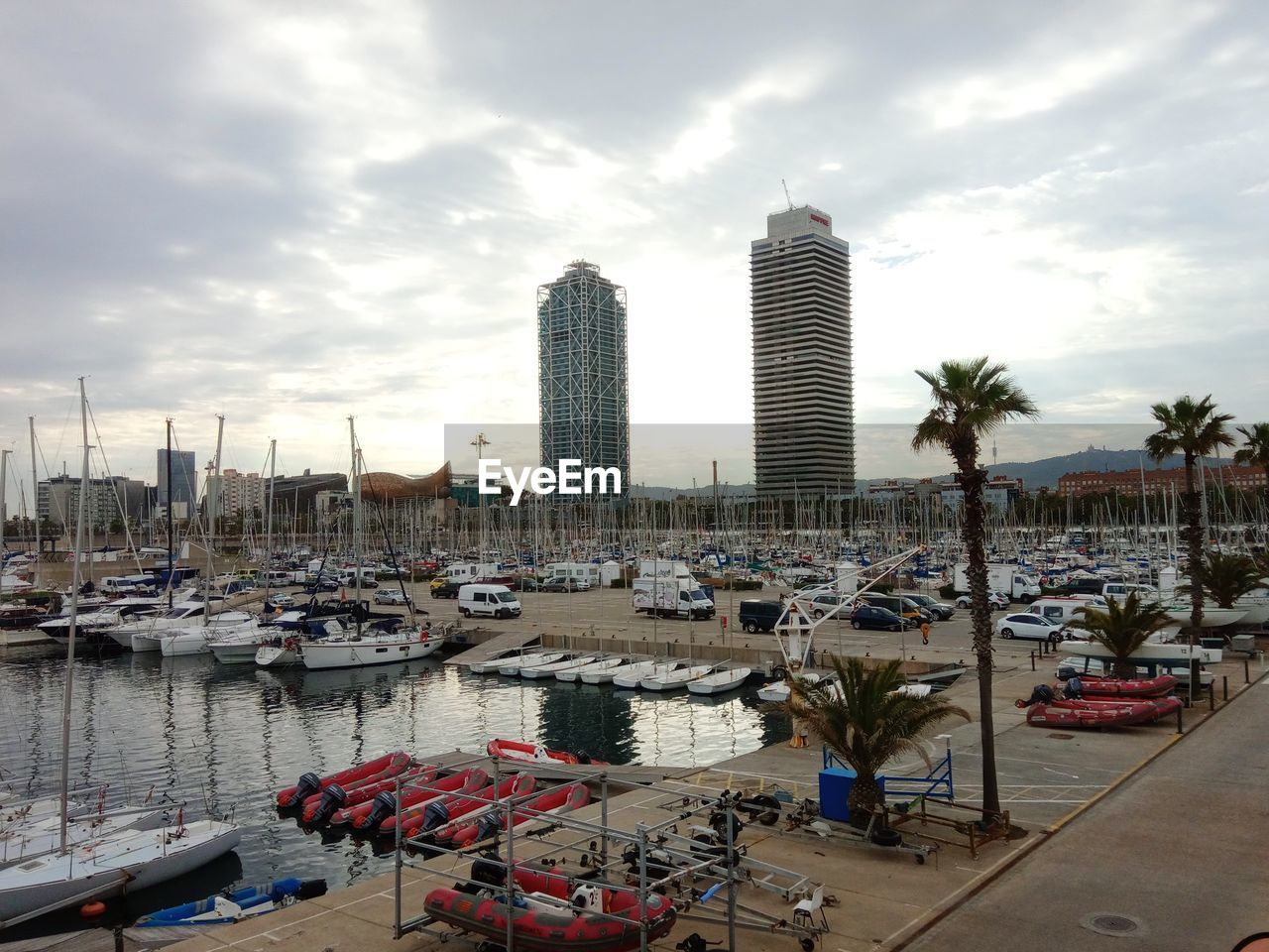 water, sky, architecture, cloud - sky, building exterior, transportation, built structure, nautical vessel, mode of transportation, city, harbor, building, nature, moored, tropical climate, palm tree, day, tree, office building exterior, skyscraper, outdoors, no people, modern, sailboat, marina, yacht, cityscape, port
