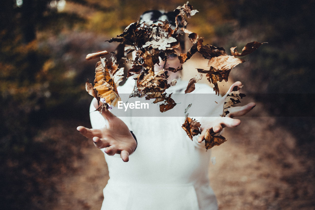 Woman Throwing Dried Autumn Leaves In Forest