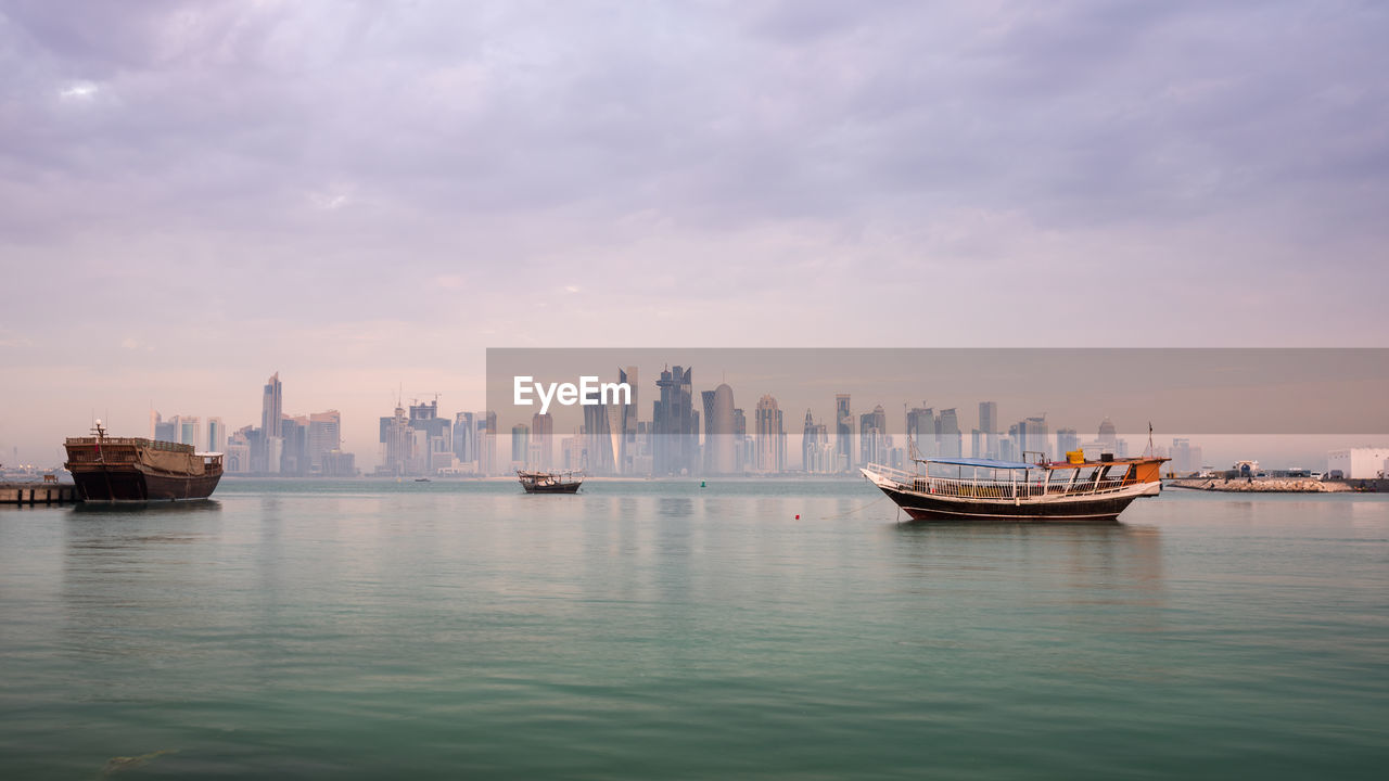 Boats in sea against sky in city