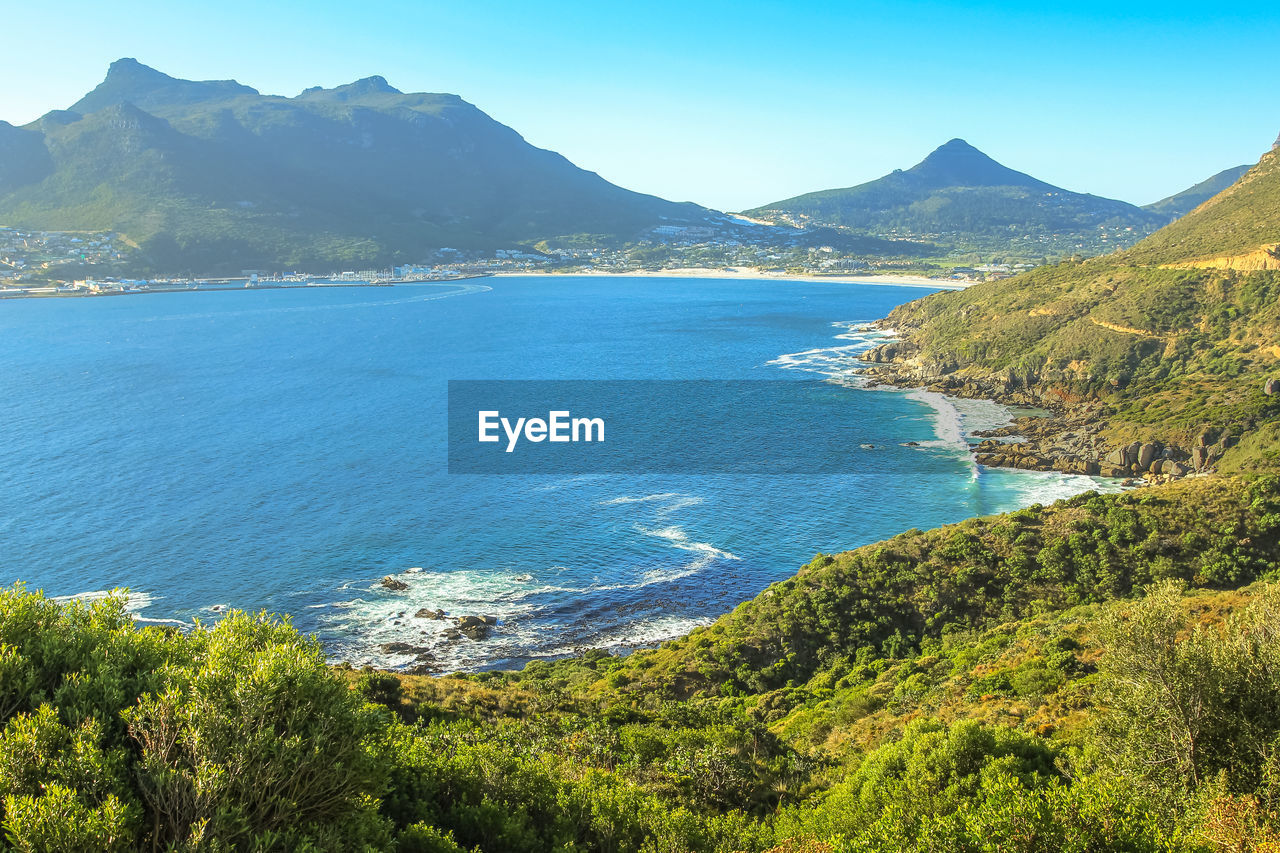 HIGH ANGLE VIEW OF SEA AND MOUNTAINS AGAINST CLEAR BLUE SKY