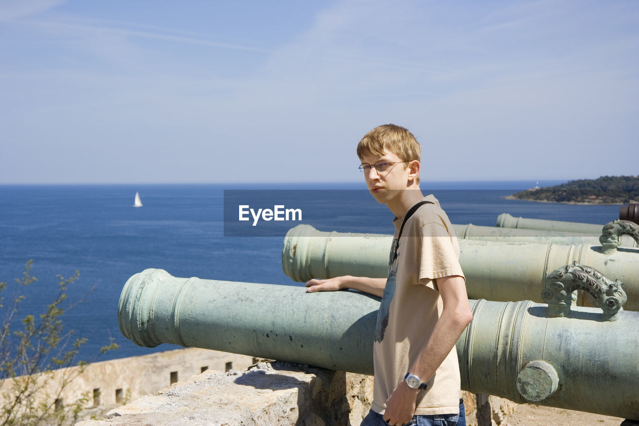 Portrait of young man standing by cannon against sea