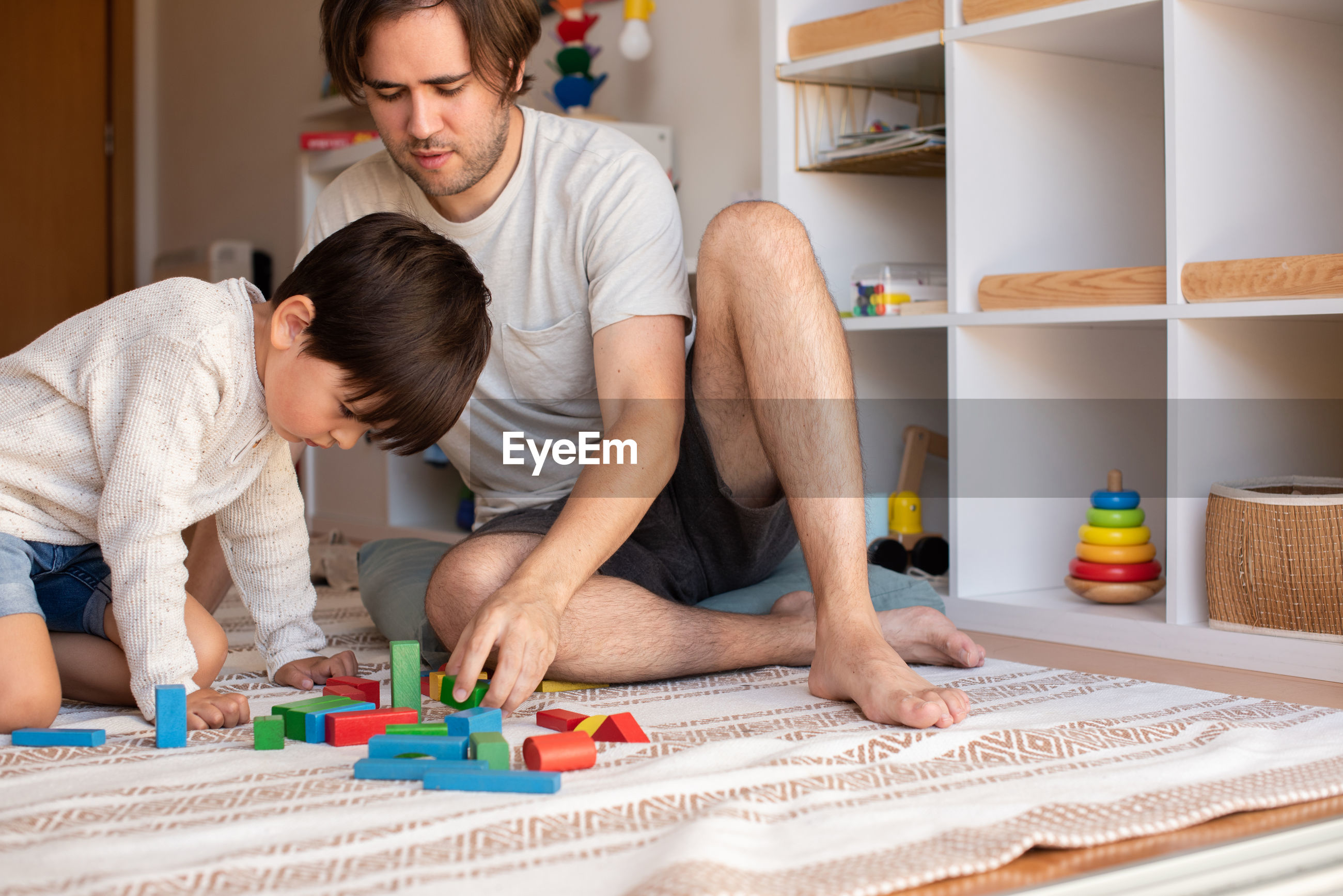 Son playing with puzzle while sitting with father at home