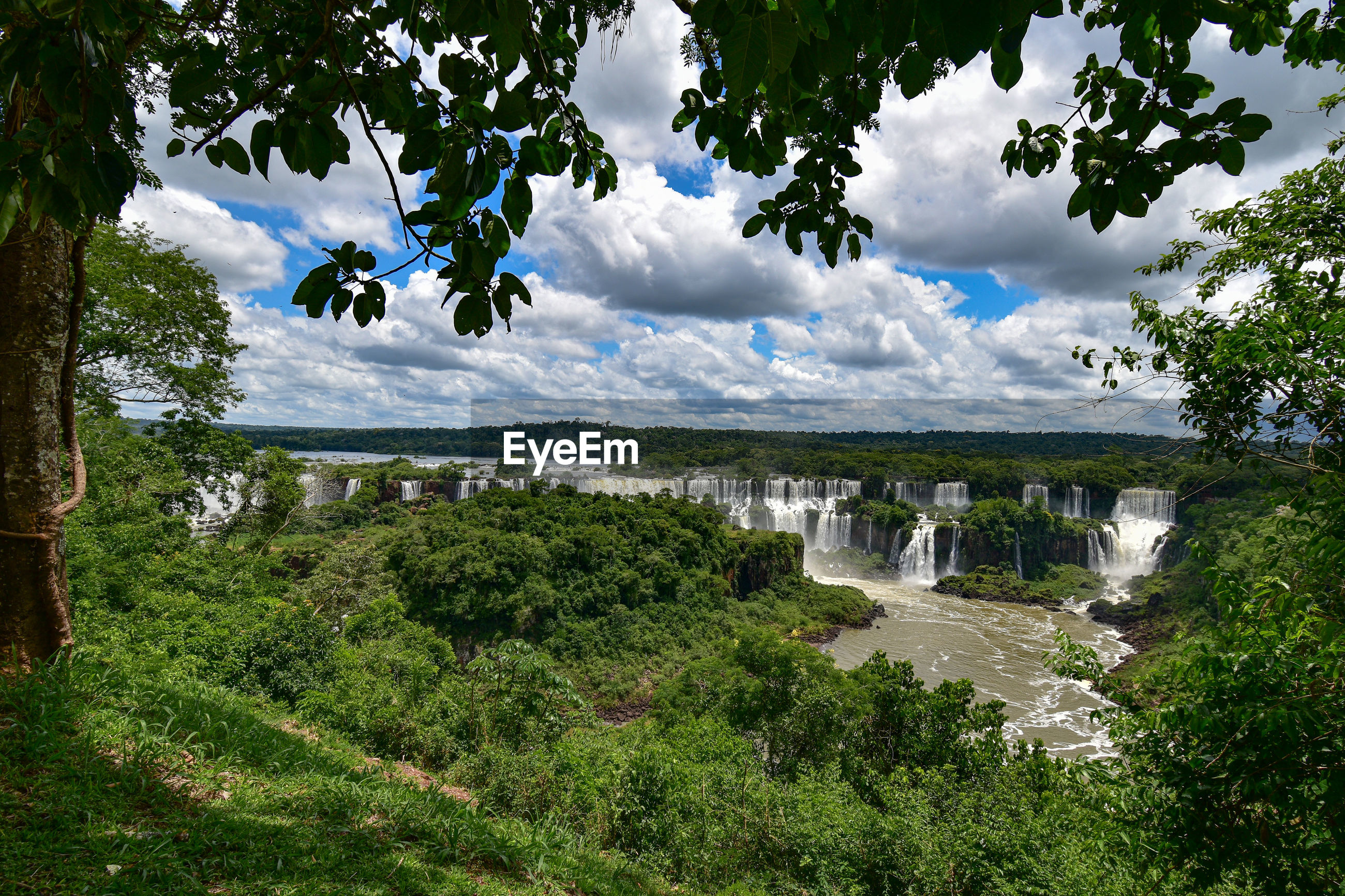 Scenic view of landscape against sky - iguazu waterfalls seen through a natural frame