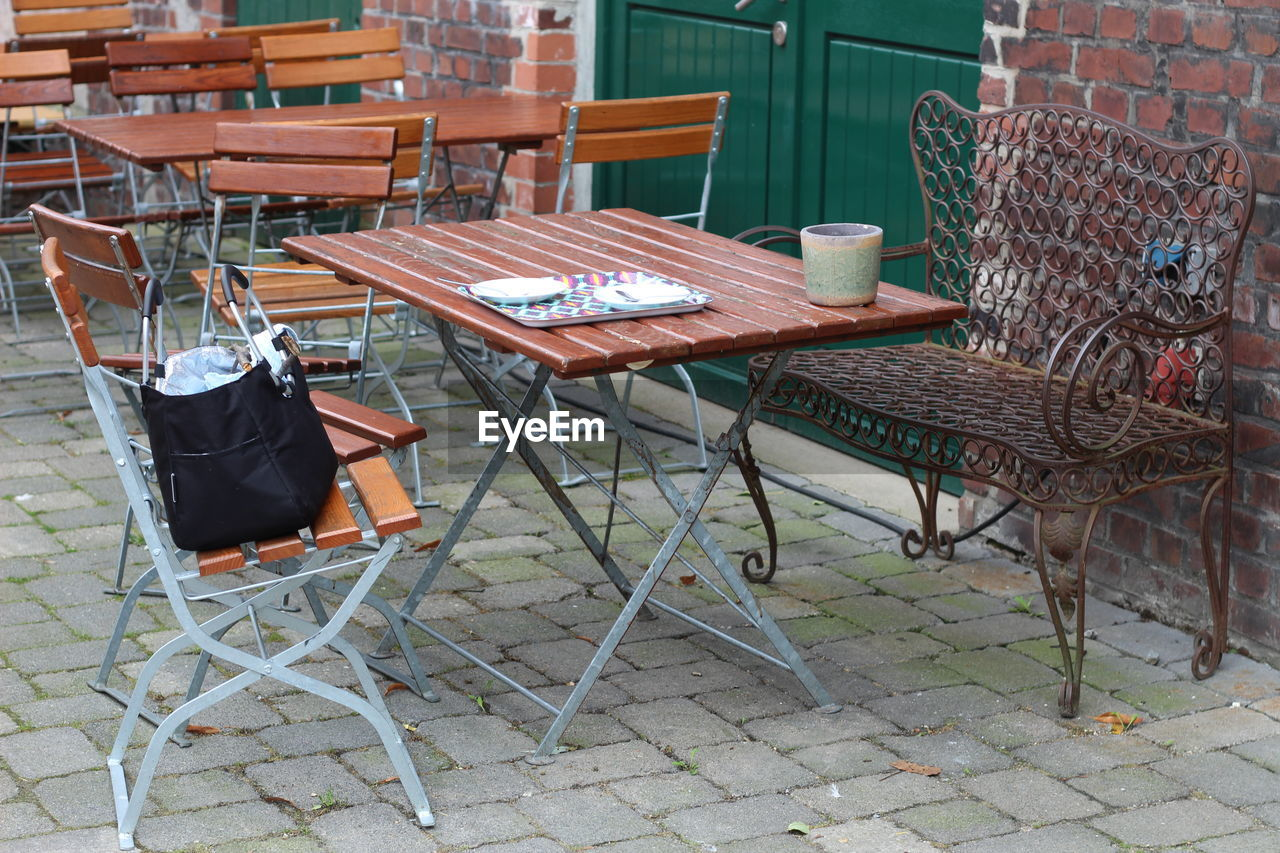 chair, seat, table, absence, cafe, empty, architecture, restaurant, business, no people, furniture, wood - material, sidewalk cafe, day, food and drink, arrangement, building, relaxation, outdoors, brown, setting