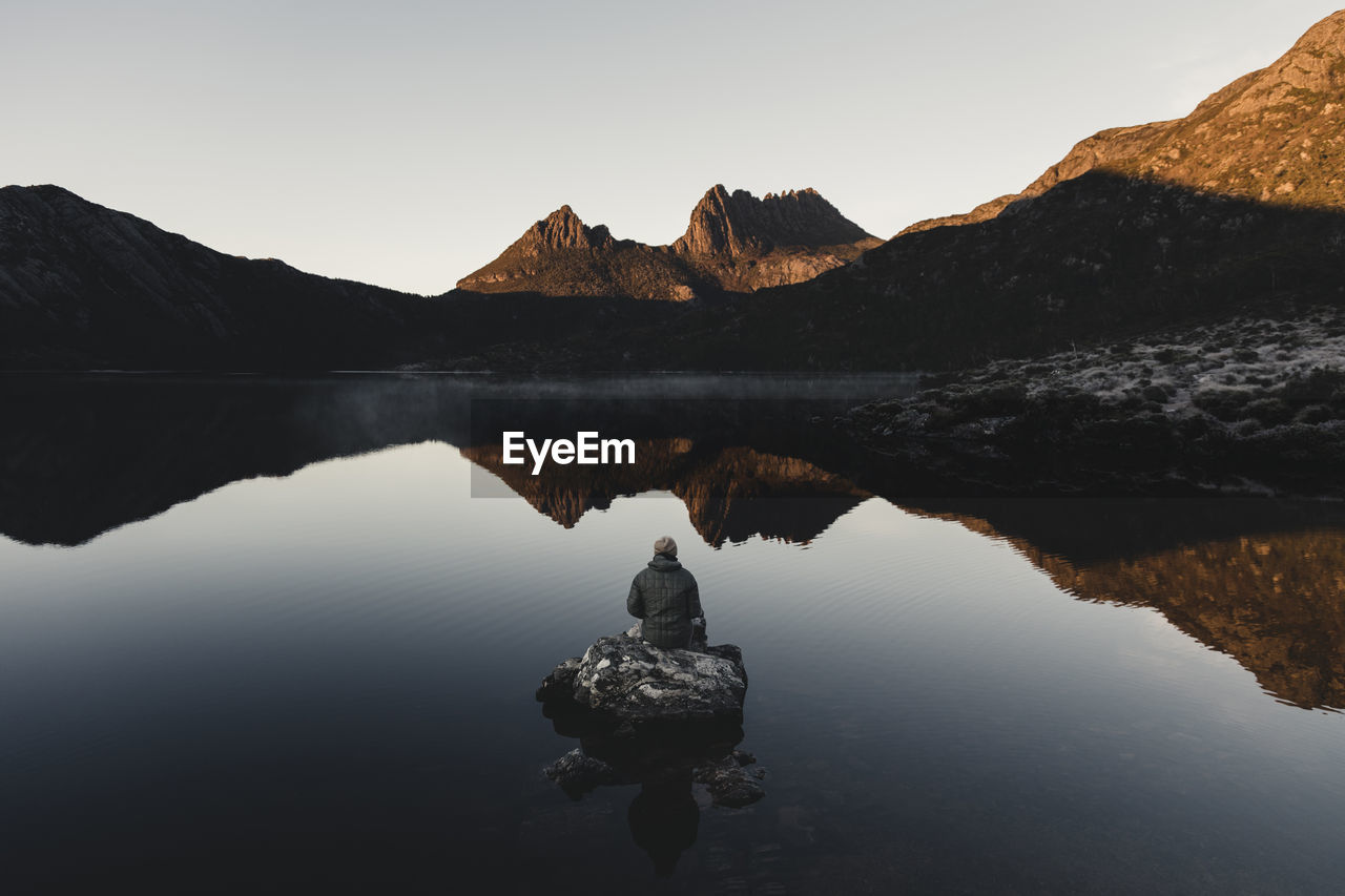 Rear View Of Person On Rock Amidst Calm Lake Against Mountain