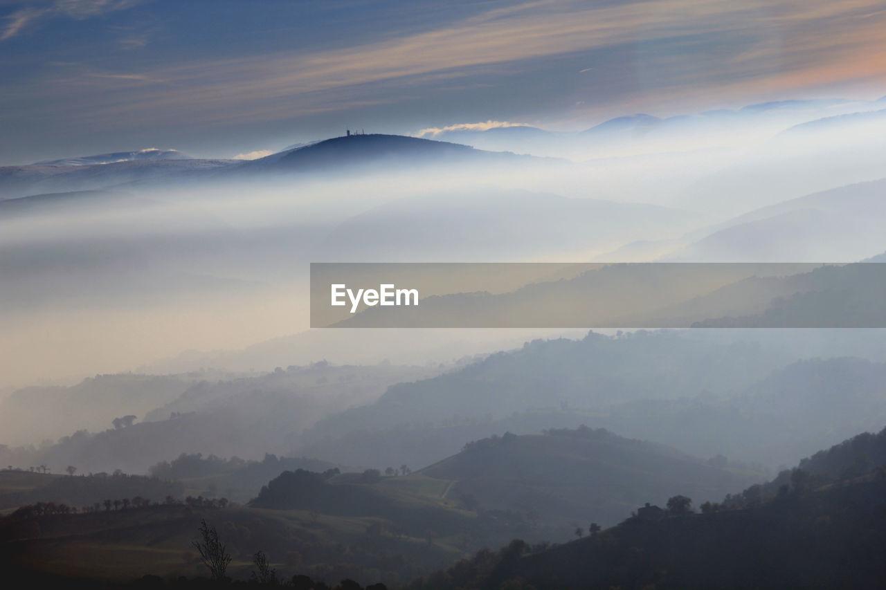 beauty in nature, mountain, scenics - nature, tranquil scene, fog, tranquility, sky, mountain range, environment, landscape, non-urban scene, cloud - sky, idyllic, nature, no people, remote, majestic, hazy, outdoors, mountain peak
