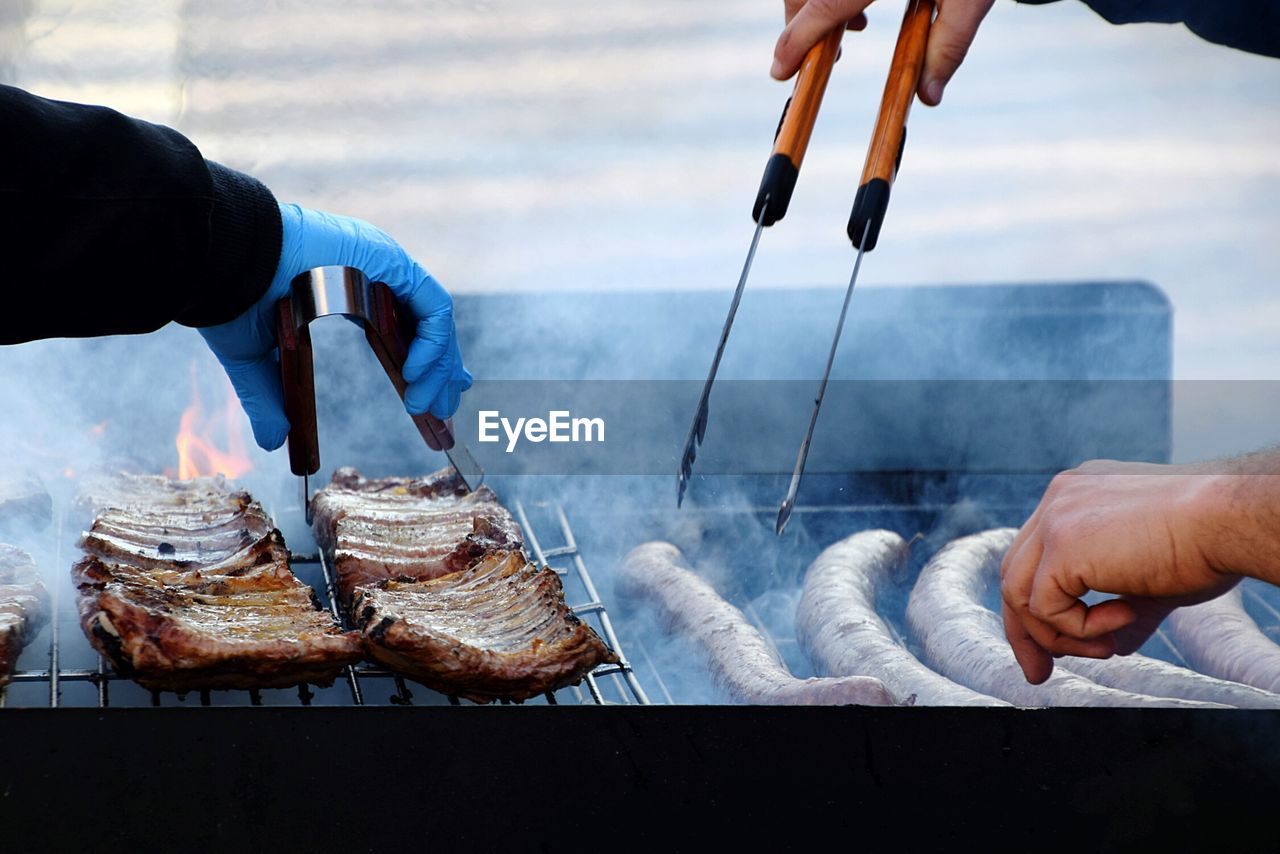 Close-Up Of Men Holding Food On Barbecue Grill