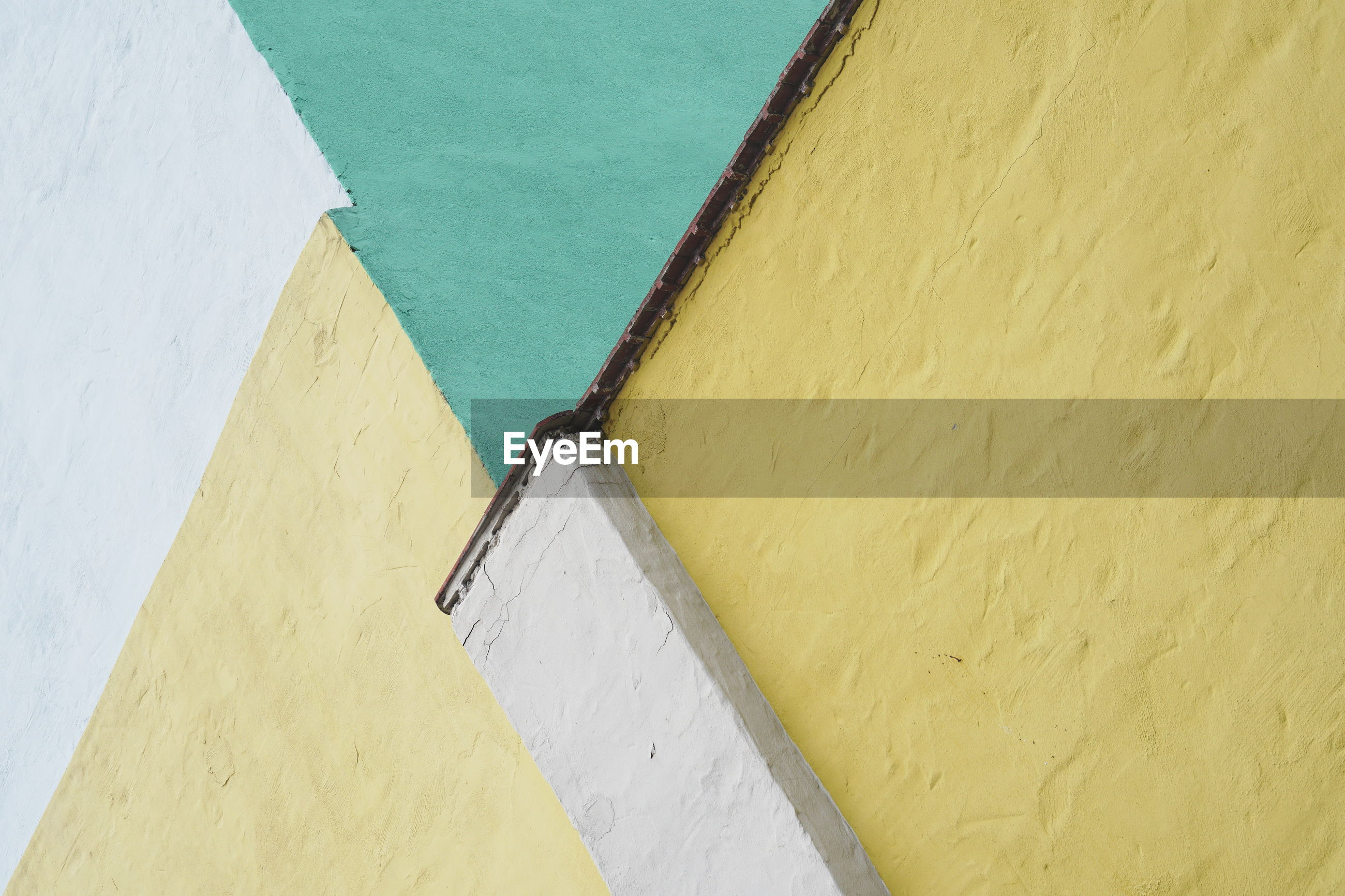 HIGH ANGLE VIEW OF WHITE WALL WITH UMBRELLA