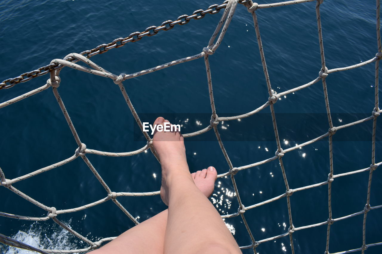 Low section of woman over sea