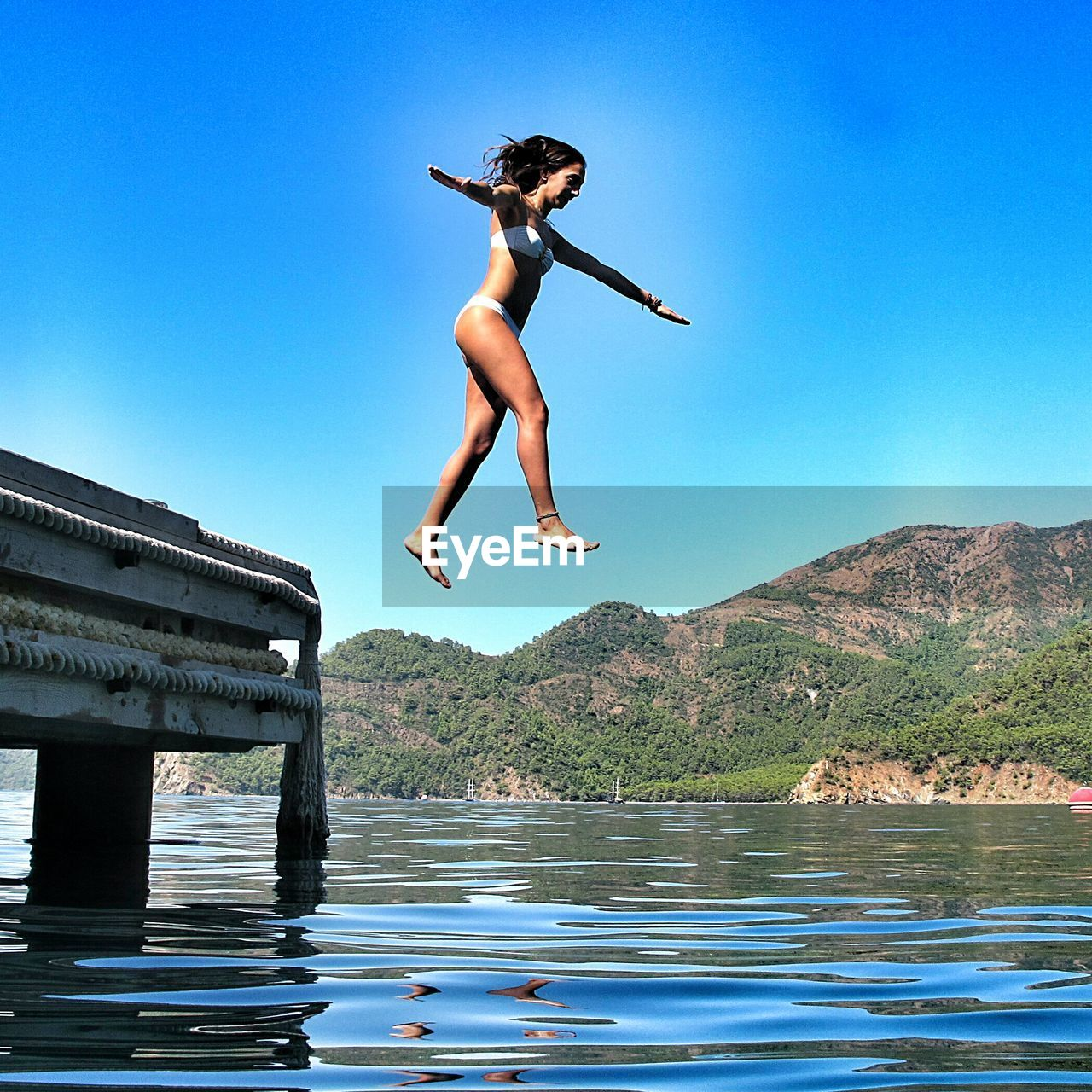 Full length of woman diving into lake against clear blue sky