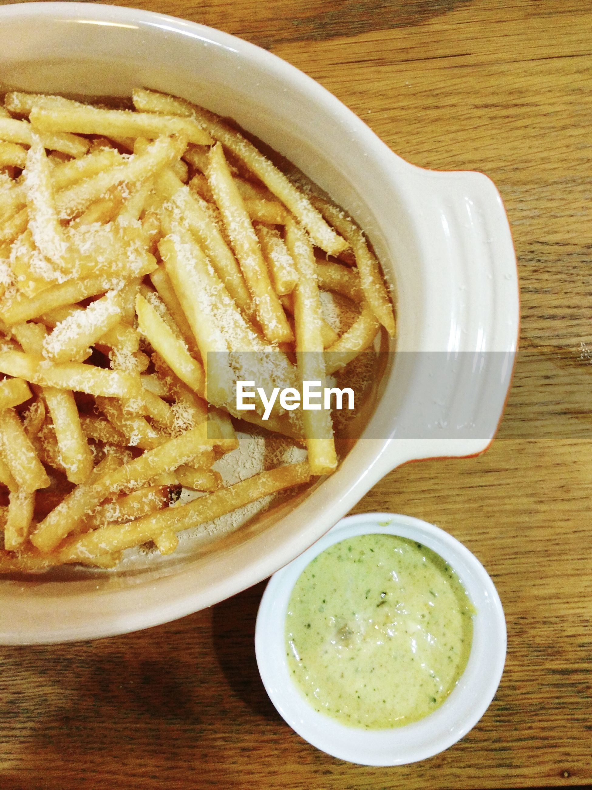 High angle view of french fries in bowl with dip on table
