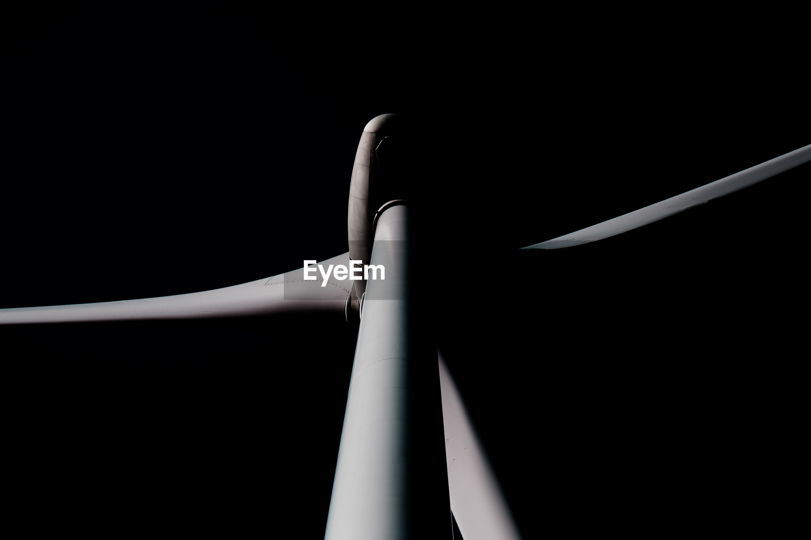 Low angle view of windmill against black background