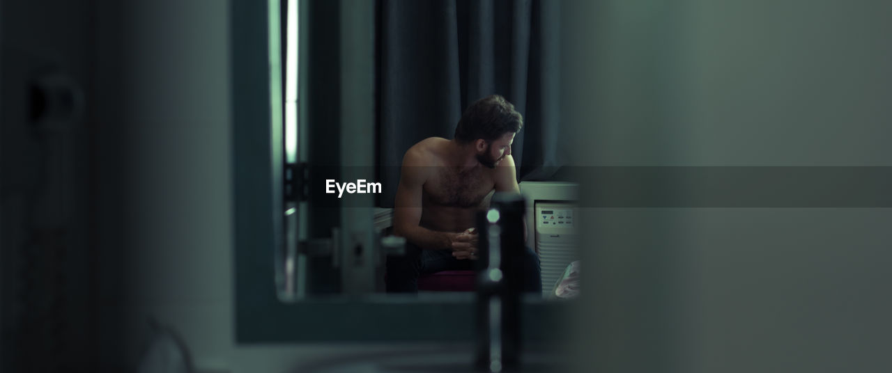 shirtless, one person, indoors, men, real people, adult, standing, focus on background, lifestyles, technology, selective focus, computer, young adult, young men, males, waist up, working, sport, three quarter length, weight training