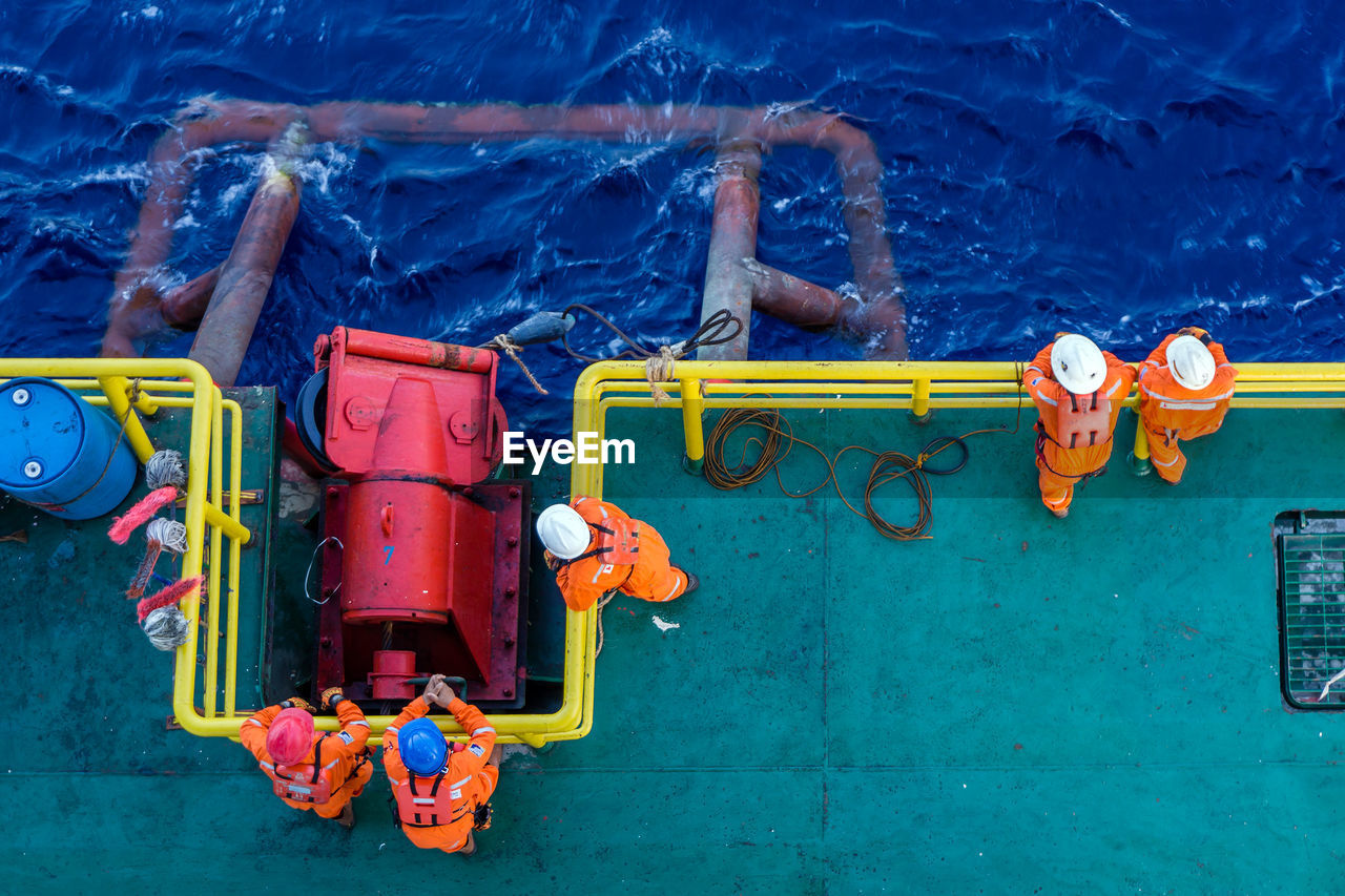 High angle view of workers standing on boat in sea
