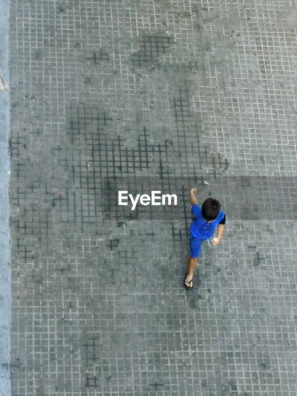 HIGH ANGLE VIEW OF MAN WALKING BY WALL