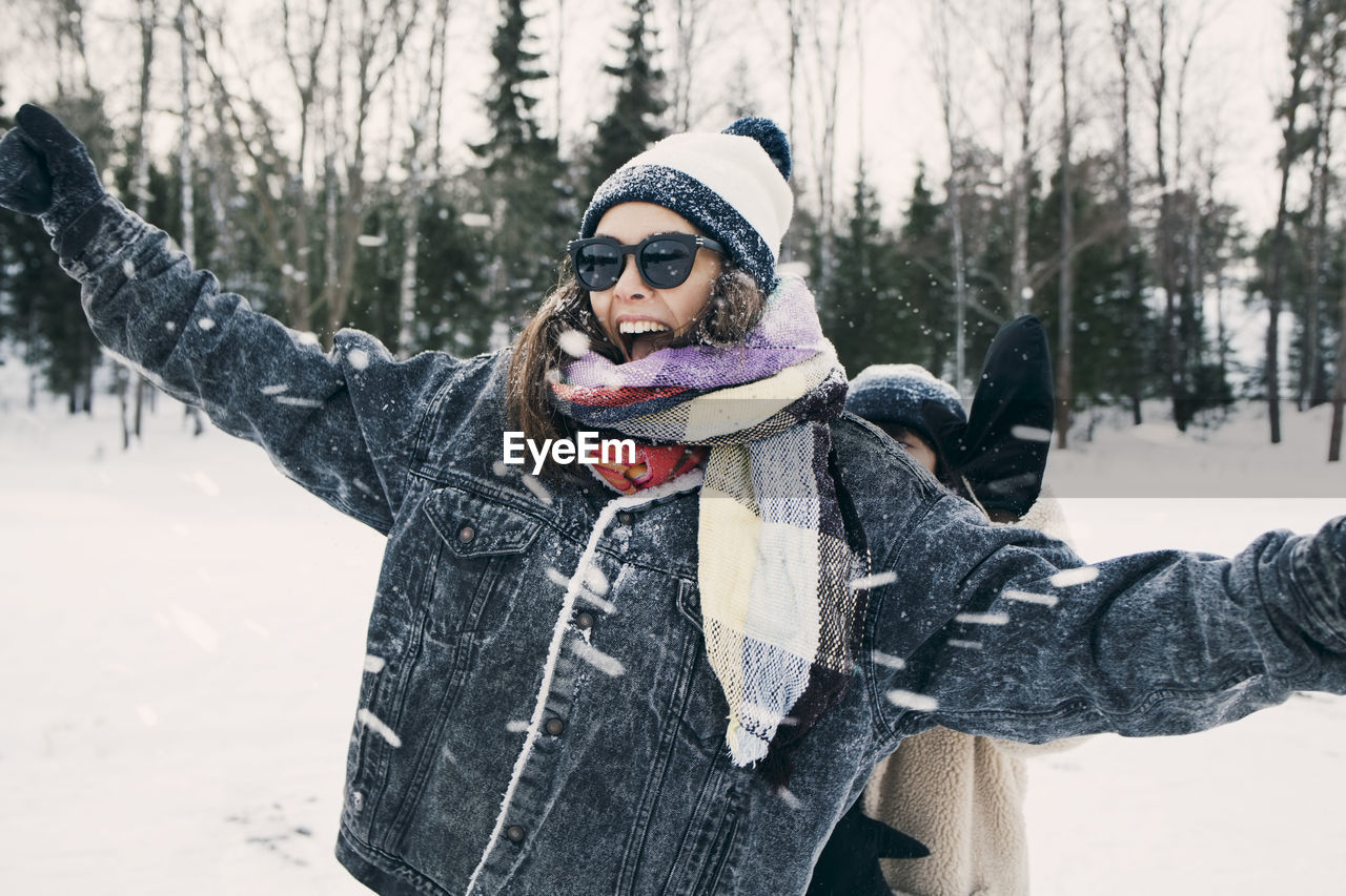winter, warm clothing, cold temperature, clothing, one person, snow, young adult, glove, young women, leisure activity, real people, women, focus on foreground, standing, lifestyles, front view, nature, scarf, outdoors, human arm, beautiful woman