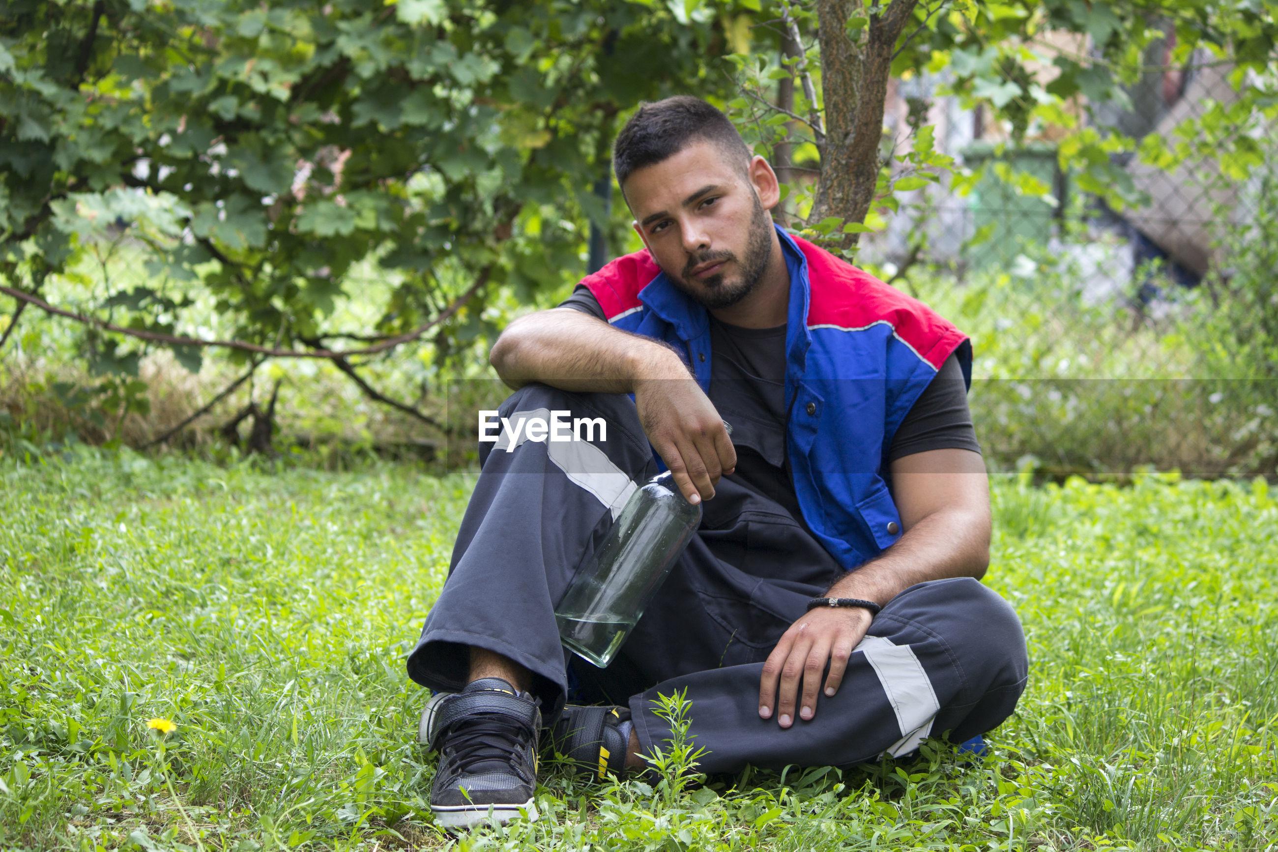 Portrait of man sitting on grass land