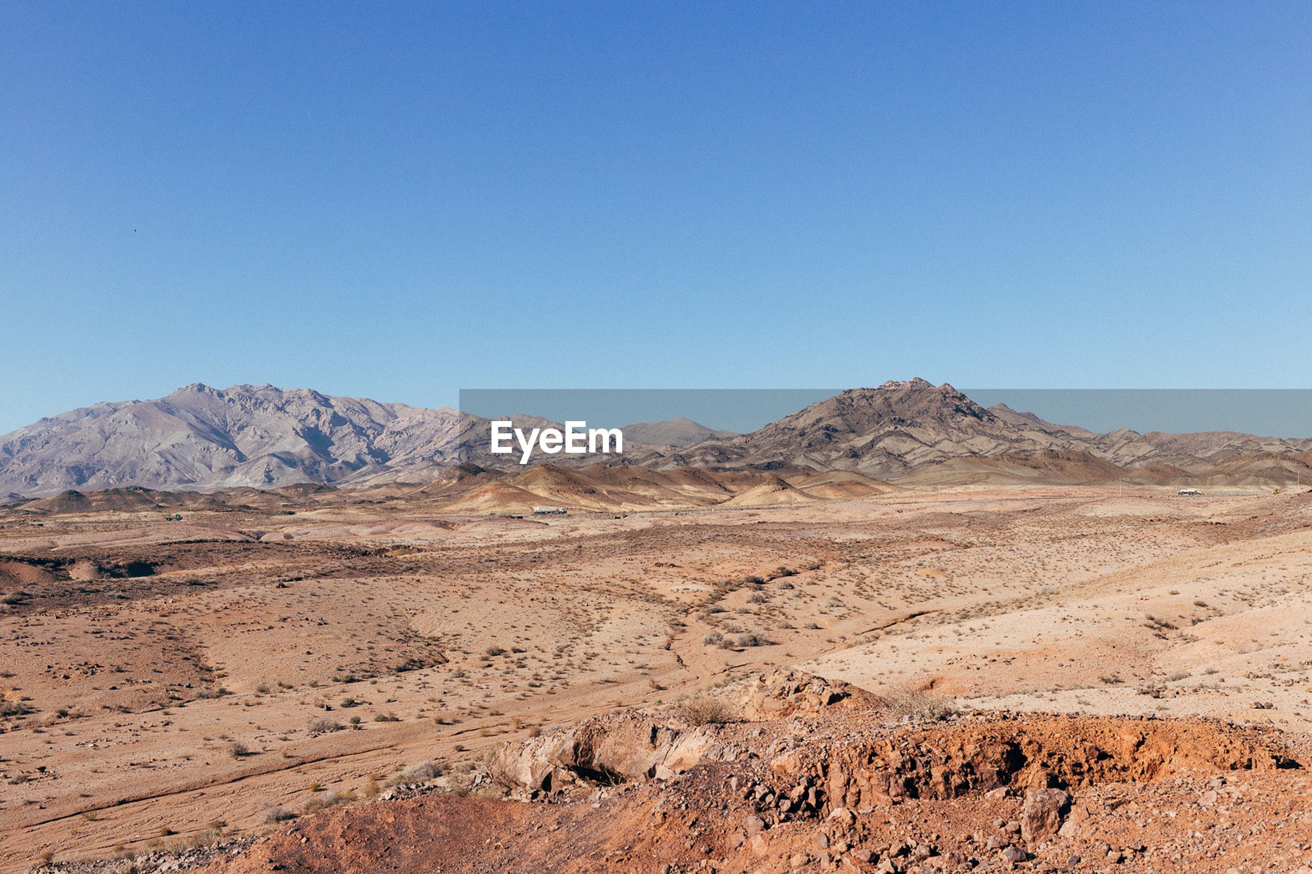 Barren landscape against clear blue sky