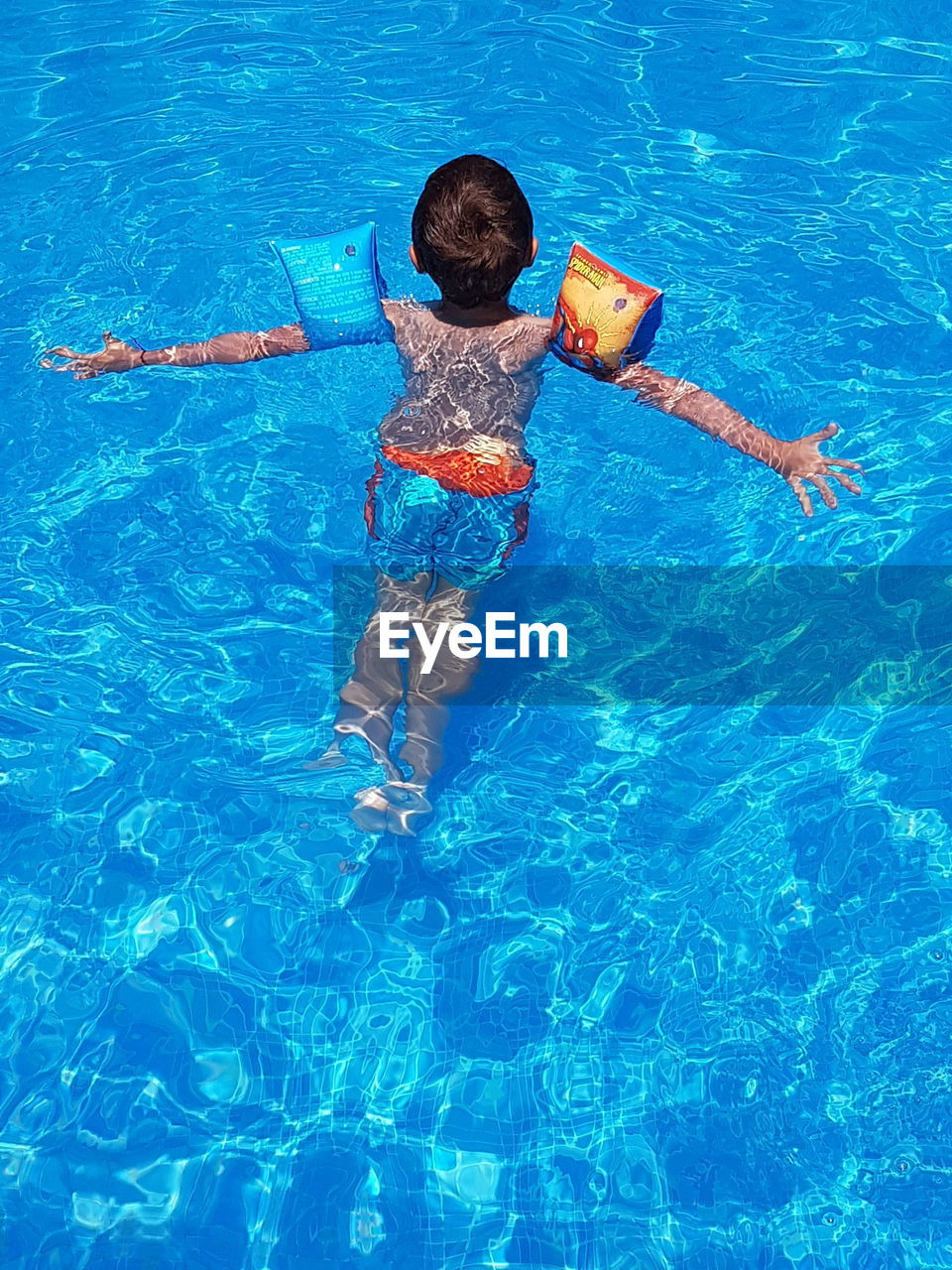 HIGH ANGLE VIEW OF BOY ON SWIMMING POOL