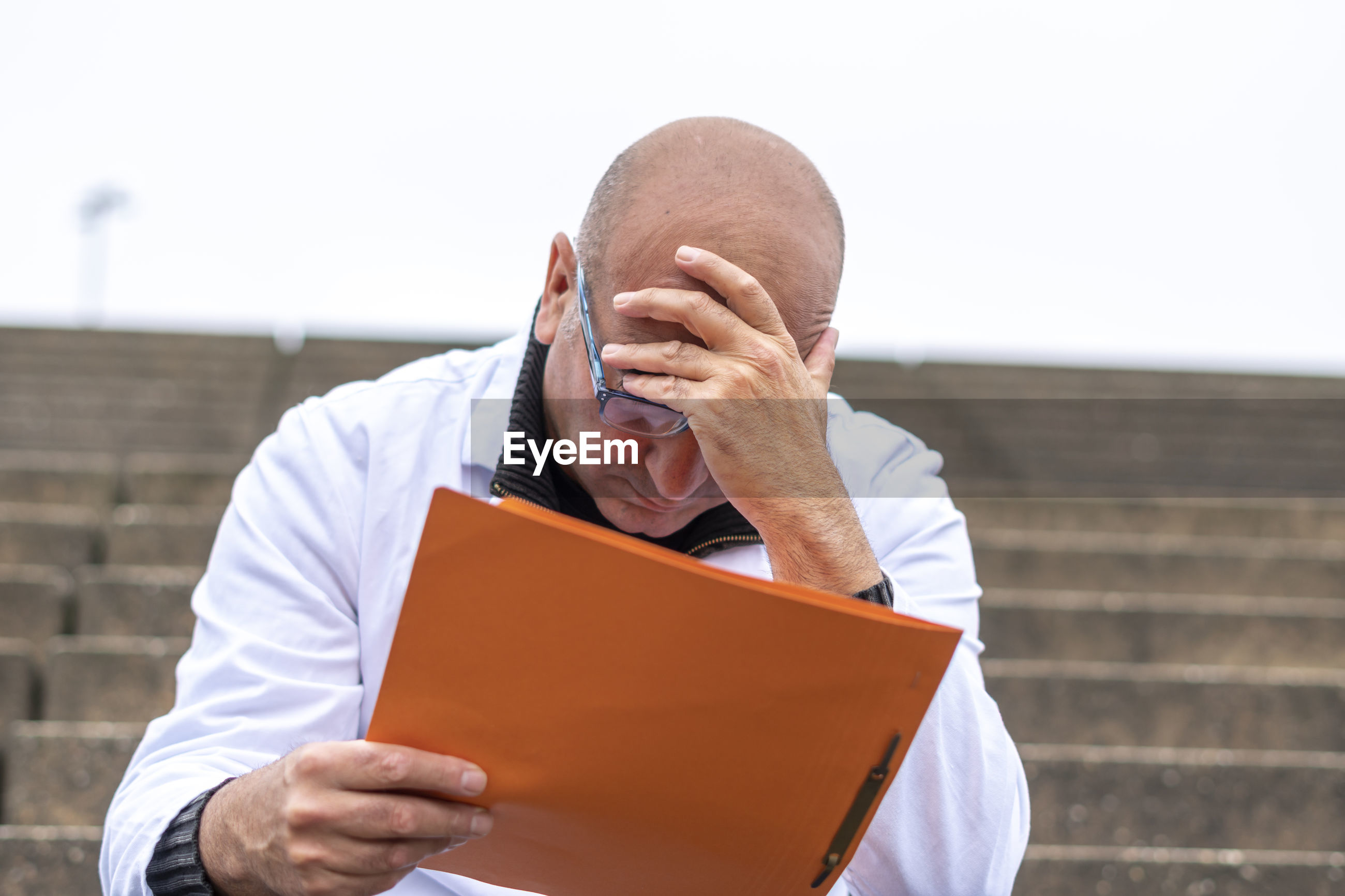 Stressed doctor holding file while sitting outdoors