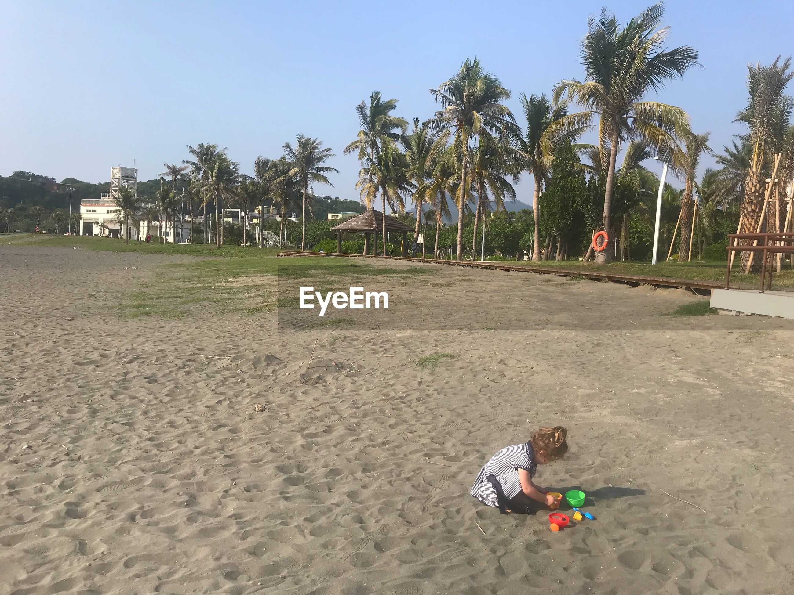 Side view of girl playing with toys at beach against clear sky