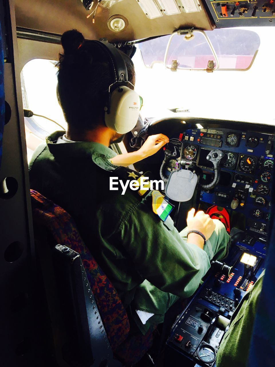 cockpit, airplane, real people, pilot, sitting, transportation, piloting, control panel, indoors, occupation, one person, air vehicle, mode of transport, uniform, day, flying, technology, people