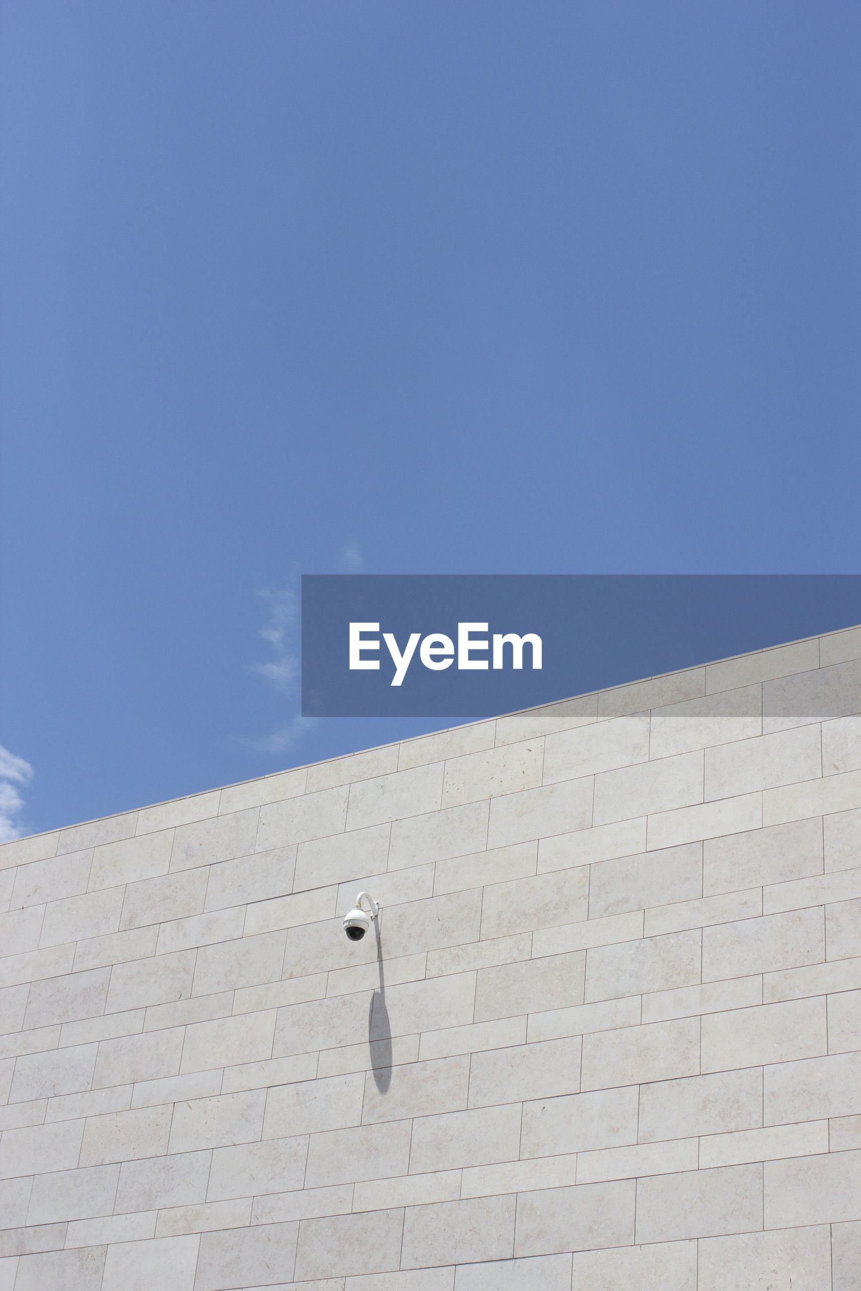 Low angle view of wall against blue sky