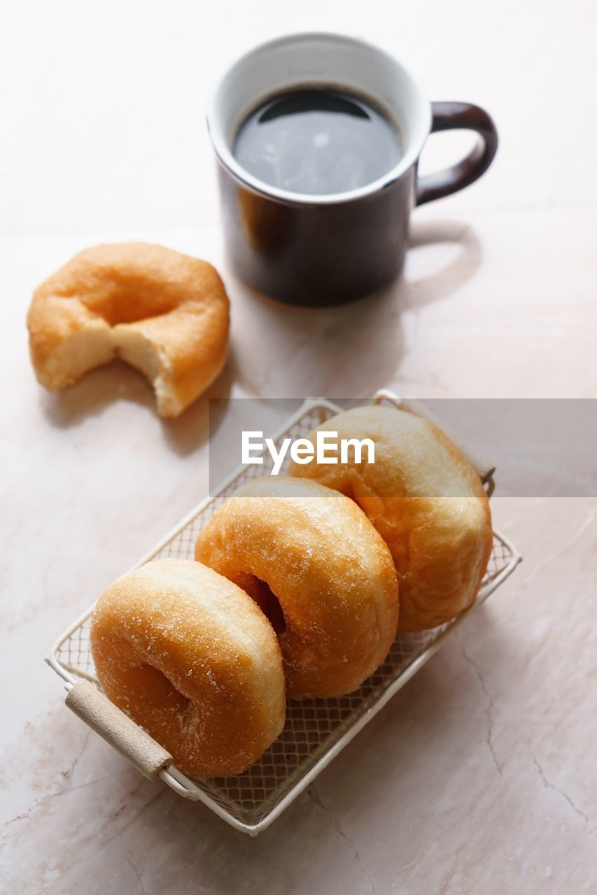 Close-Up Of Coffee And Donuts On Table