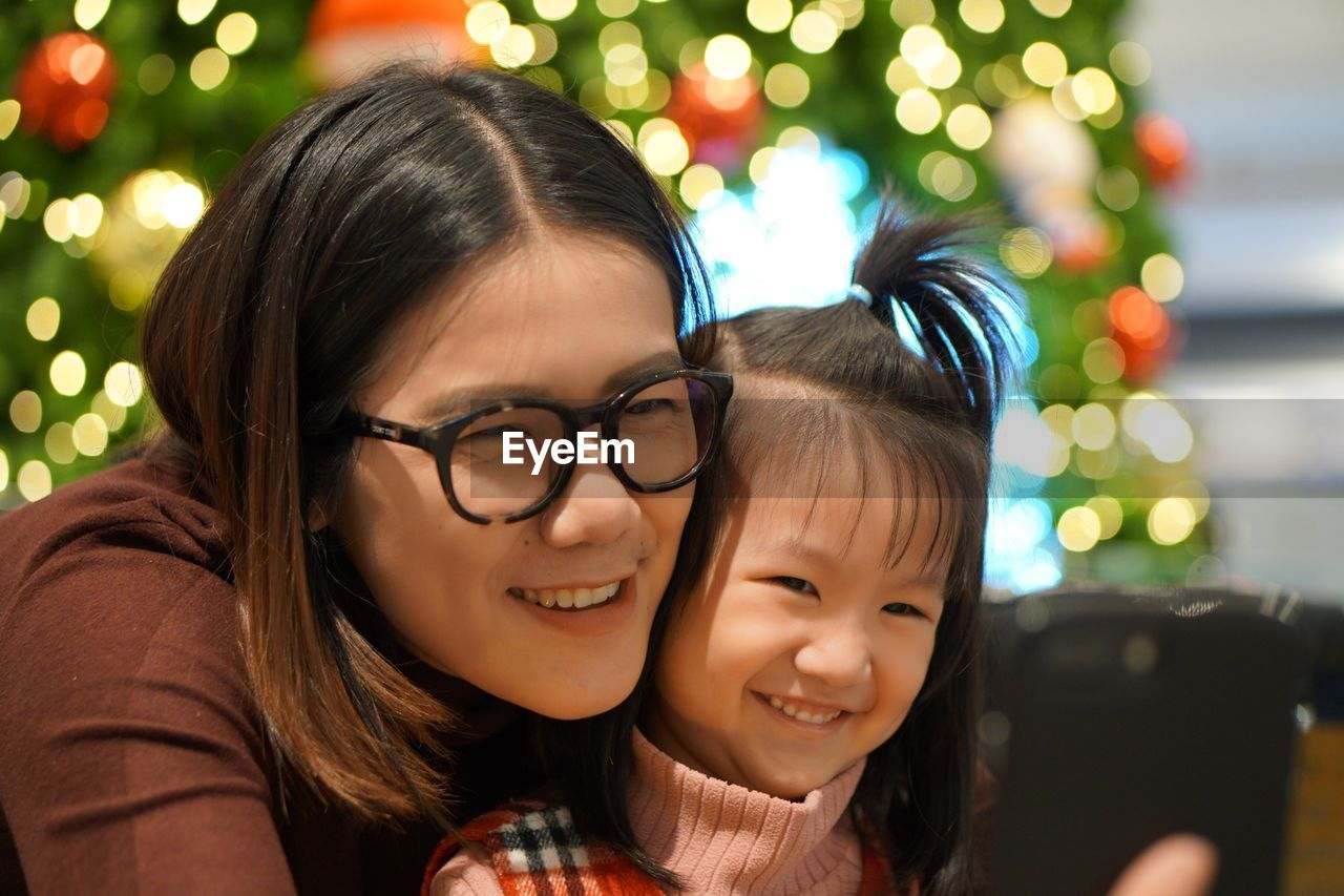 Portrait Of Happy Mother With Daughter Against Defocused Lights