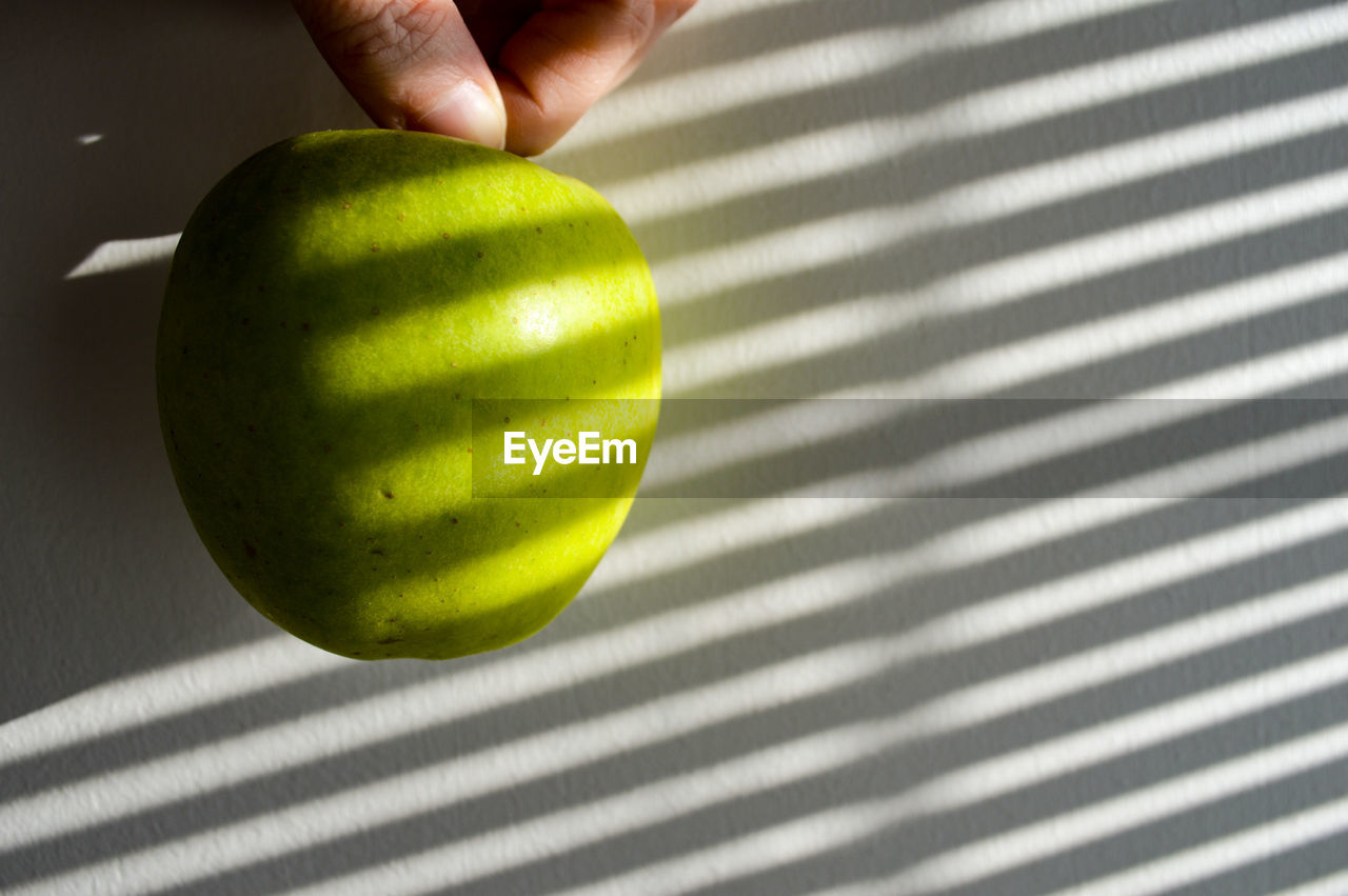 human hand, fruit, apple - fruit, striped, human body part, human finger, food and drink, food, green color, granny smith apple, one person, healthy eating, real people, holding, healthy lifestyle, table, indoors, shadow, lifestyles, sunlight, leisure activity, men, freshness, close-up, day, people, adult, adults only