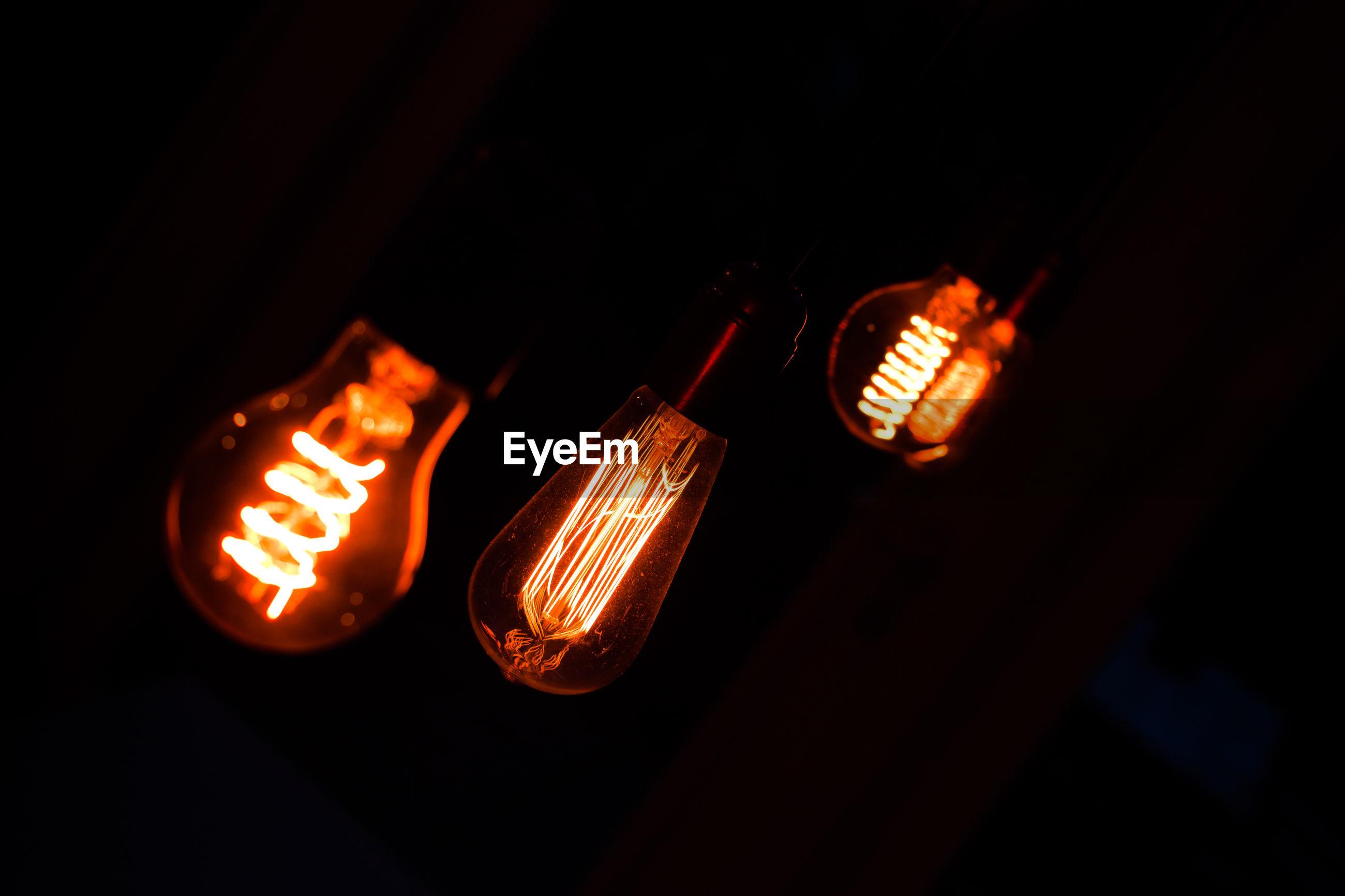 Close-up of illuminated lighting bulbs against black background