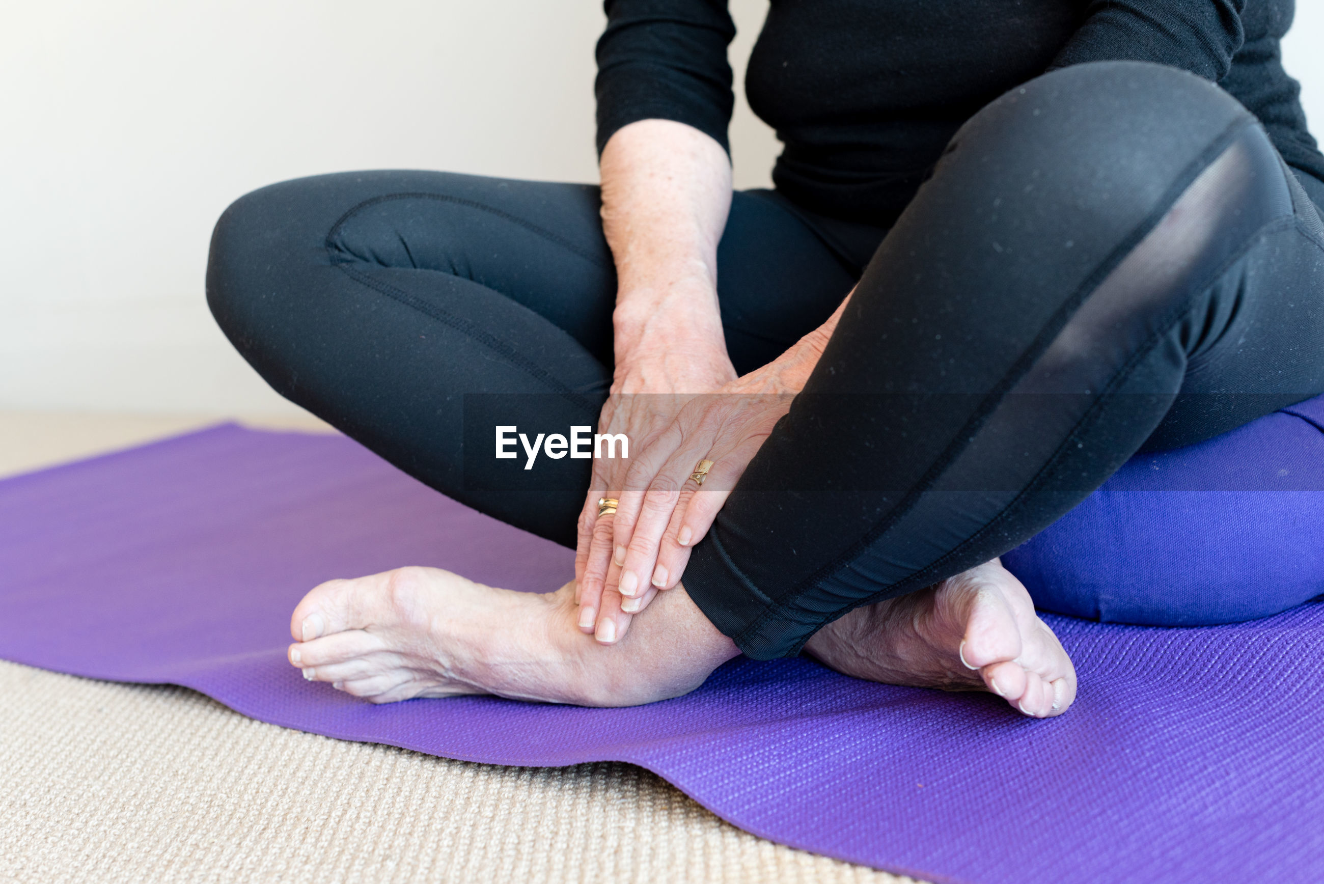 Low section of woman doing yoga on exercise mat