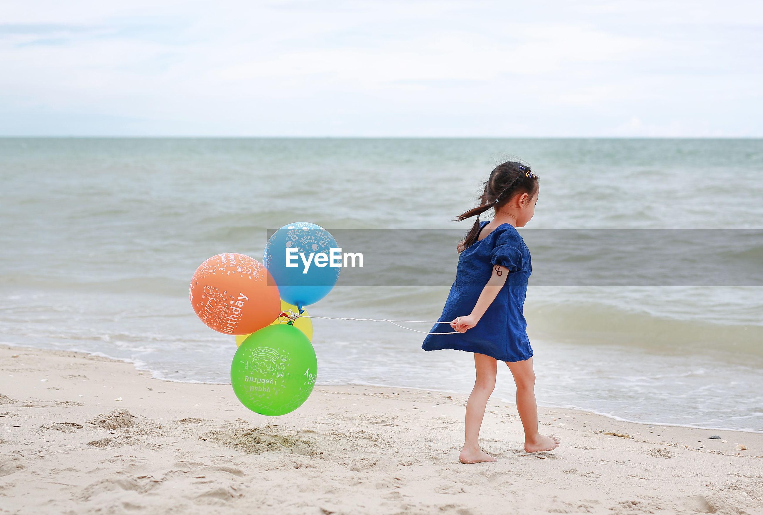 Girl with balloons walking at beach