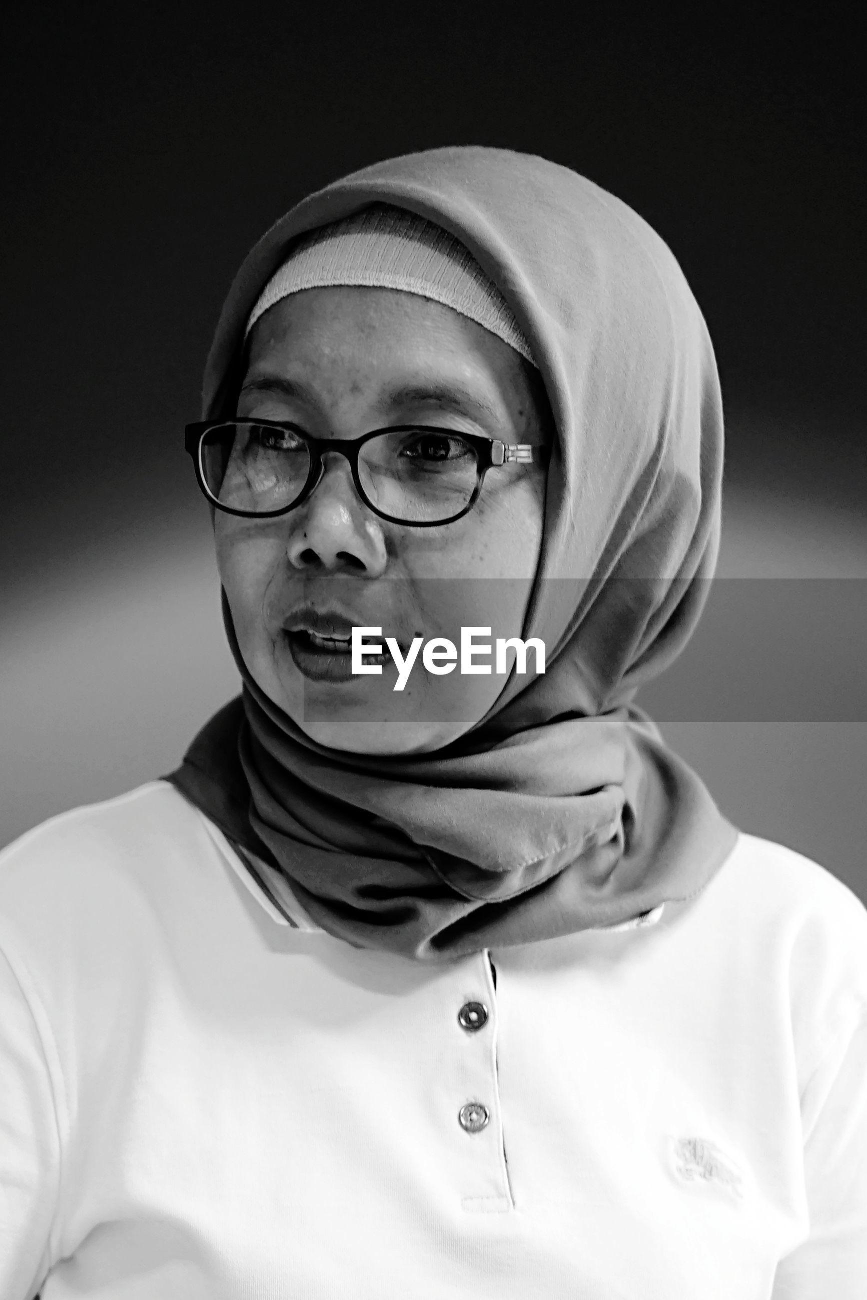 Woman looking away against black background