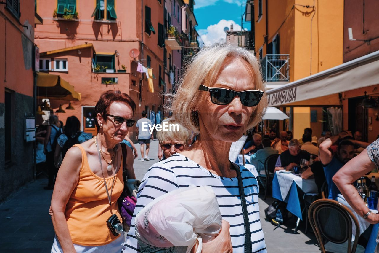 glasses, sunglasses, fashion, architecture, city, built structure, people, adult, building exterior, women, leisure activity, lifestyles, incidental people, females, mid adult, casual clothing, real people, smiling, portrait