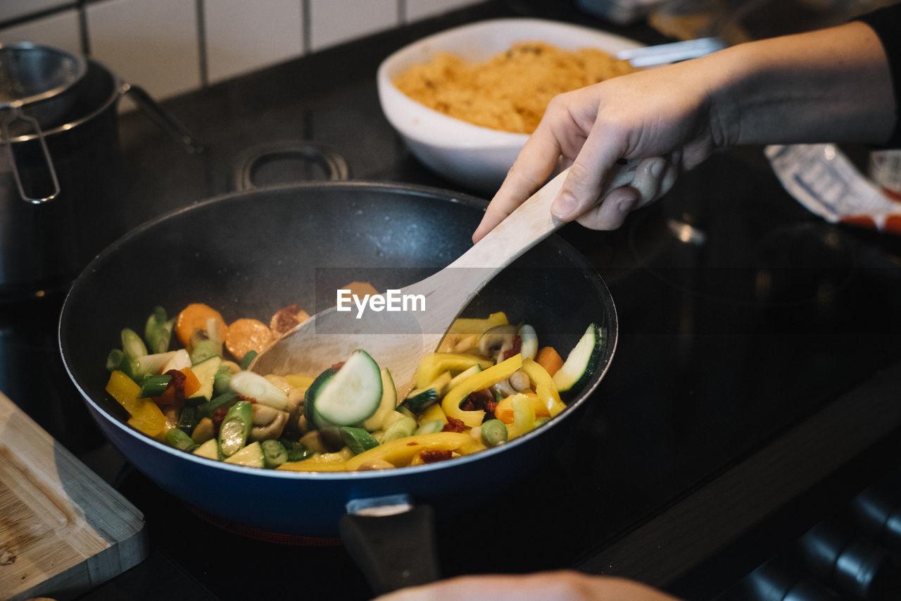 PERSON PREPARING DINNER IN KITCHEN