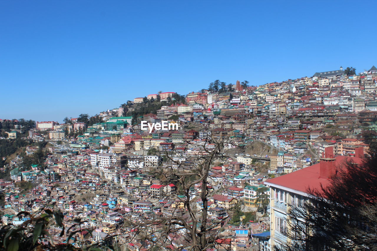Buildings in city against clear blue sky