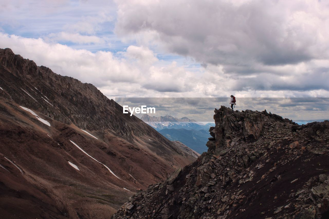 Scenic view of mountains and hiker against sky
