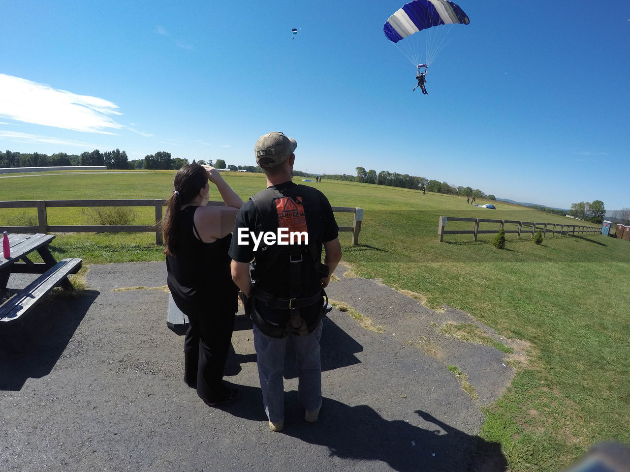 grass, field, leisure activity, real people, day, rear view, men, sunlight, two people, lifestyles, sky, adventure, shadow, parachute, sport, outdoors, landscape, clear sky, nature, paragliding, people, adult