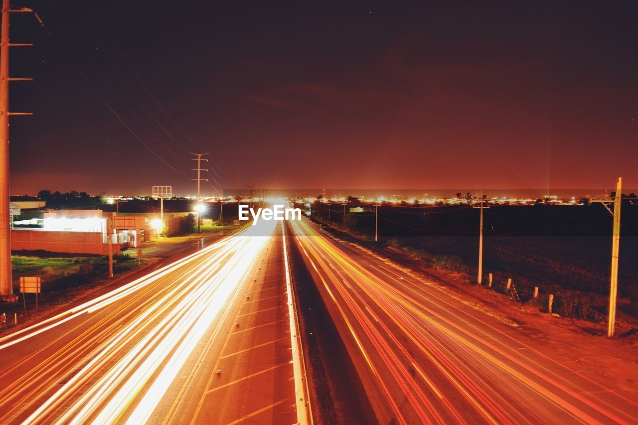 illuminated, motion, transportation, long exposure, night, speed, road, city, light trail, architecture, blurred motion, street, no people, sky, built structure, the way forward, direction, nature, city life, high angle view, outdoors, multiple lane highway