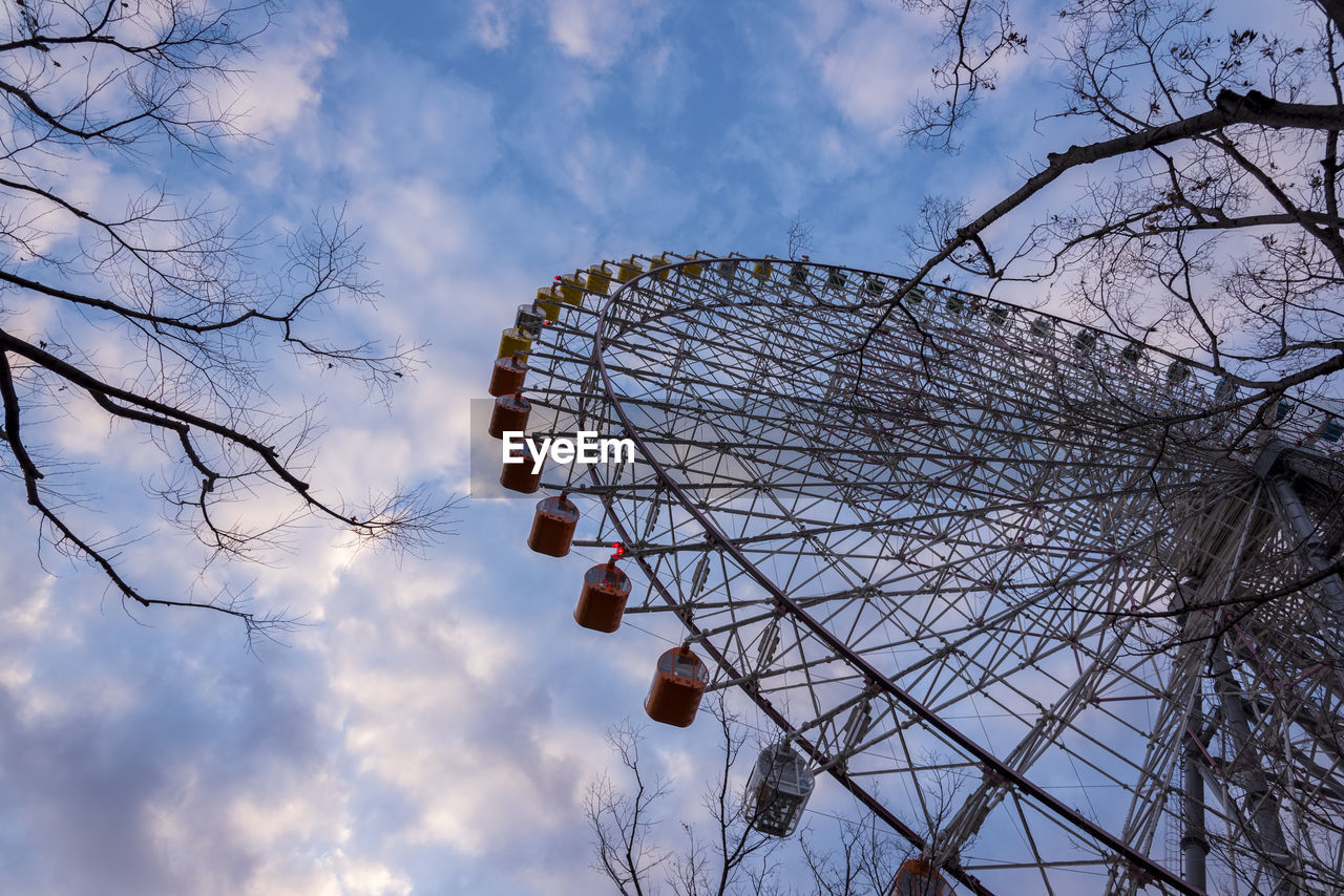 LOW ANGLE VIEW OF FERRIS WHEEL AGAINST BARE TREES