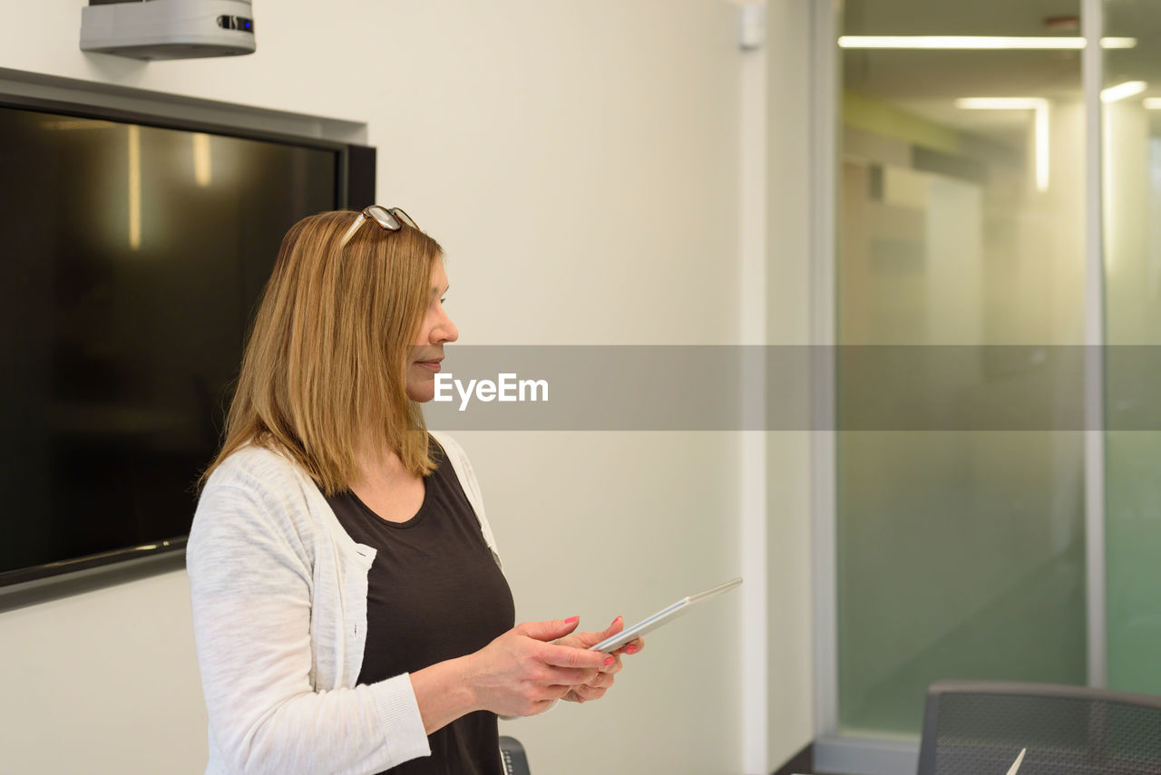 Businesswoman using digital tablet while standing in office